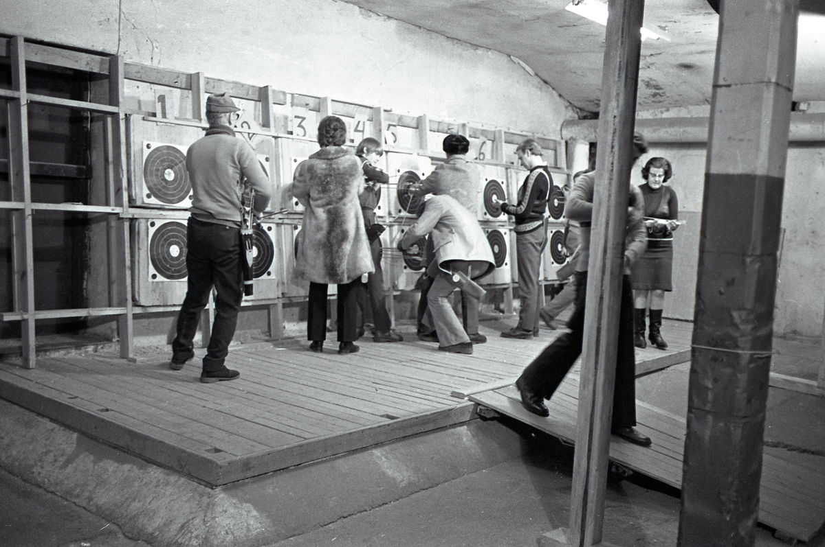 Inomhusträning hos bågskytteklubben. Skyttarna plockar loss sina pilar ur måltavlorna. Måltavlorna sitter, i dubbla rader, på kortsidan. Lokalen förefaller vara belägen i en källare.