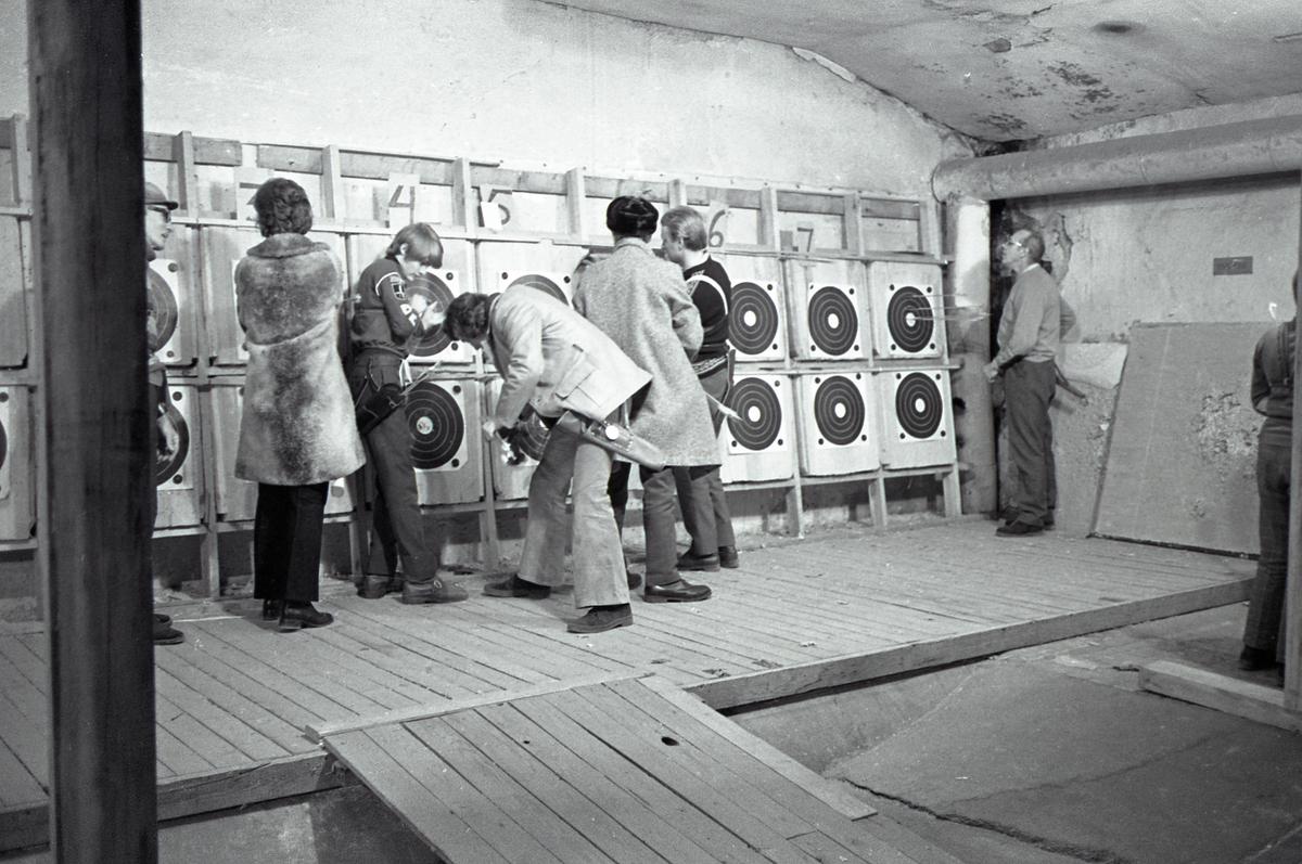Inomhusträning hos Arboga Bågskytteklubb. Måltavlorna är monterade i dubbla rader längs kortväggen av källarlokalen. Skyttarna plockar bort pilarna och räknar poäng. Flera, av skyttarna, har sitt koger hängande vid höften. Två personer bär ytterkläder.