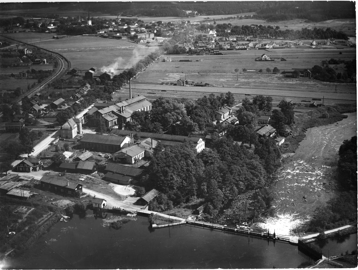 Flygfoto över Arboga Mekaniska Verkstad.  Bilden visar Mekenområdet, dammen i förgrunden och Arbogaån till höger. Järnvägen löper till vänster. Längre bort ligger Arboga stad och Heliga Trefaldighetskyrkan ses i övre vänstra hörnet.  Baksidan av fotot, se bild 00737  Arboga Mekaniska Verkstad var först i landet med att installera en elektrisk motor för drift av verktygsmaskiner vid en taktransmission (1887). Läs mer om Meken: bebyggelseregistret.raa.se, industriinventering i Västmanland Hembygdsföreningen Arboga Minnes årsbok från 1982