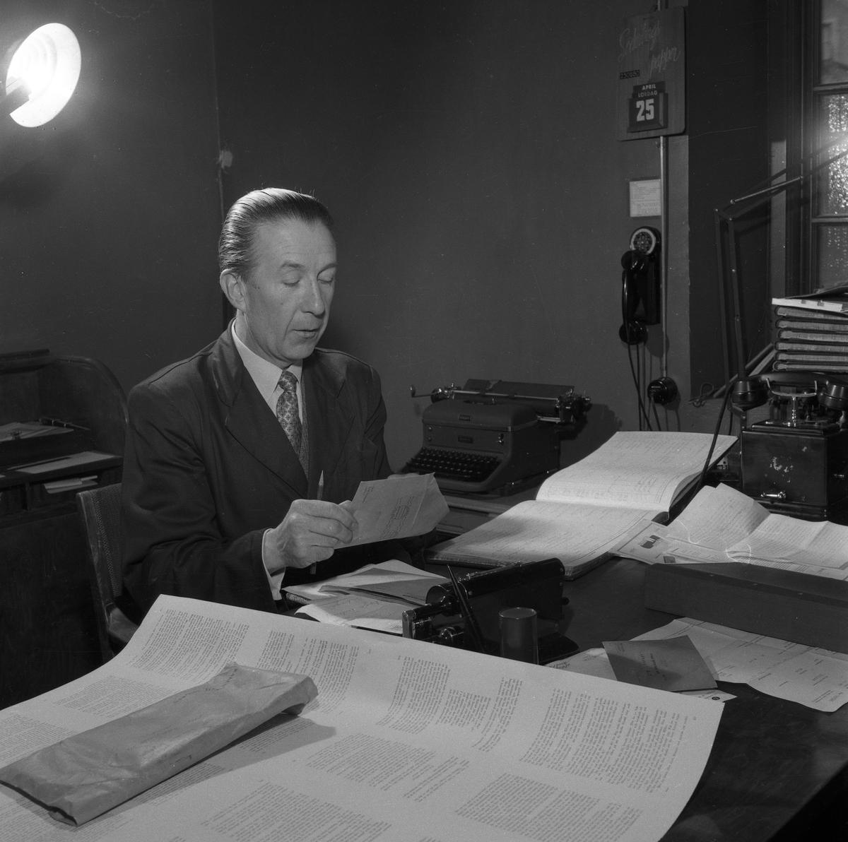 Arboga Tidning, interiör. En man, iklädd kavaj och slips, sitter vid ett skrivbord. Han har mycket papper omkring sig. Nu öppnar han ett kuvert. På bordet står en telefon. En annan telefon (möjligen en interntelefon) hänger på väggen.