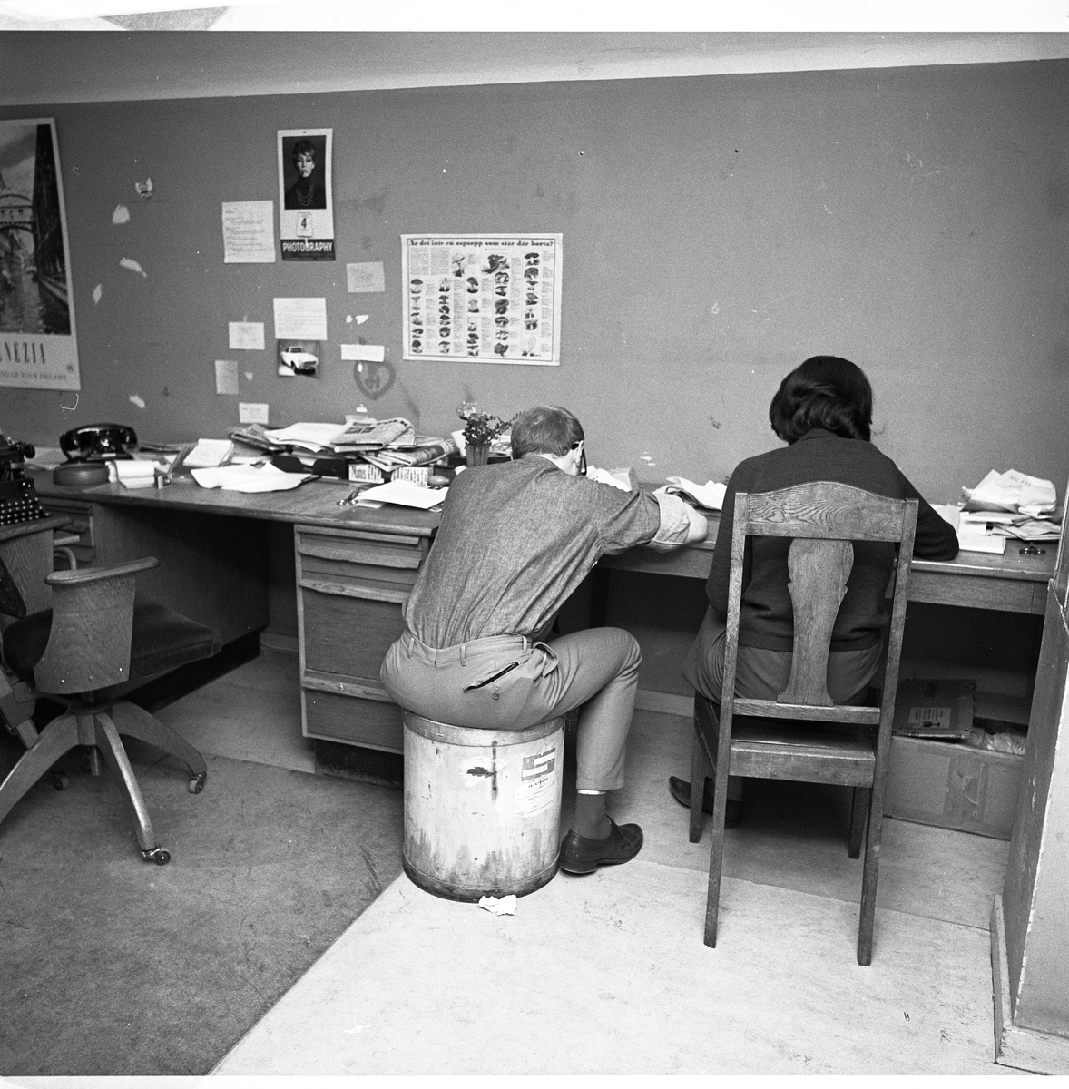 Arboga Tidning, personal och interiör. Två journalister arbetar vid samma skrivbord.  De har ryggen mot fotografen. Mannen sitter på en papperskorg och kvinnan på en trästol. Till vänster om dem finns en obemannad arbetsplats med en telefon och en arbetsstol på hjul. En skrivmaskin skymtar. På väggen sitter bland annat en affisch med olika svampar.