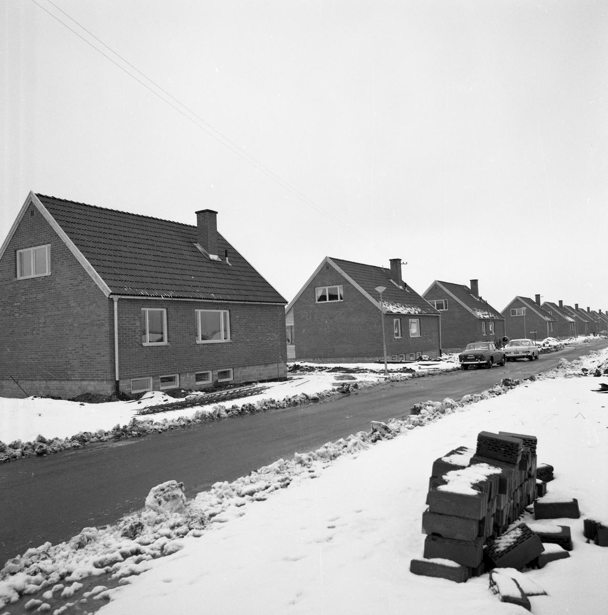 Nybyggda villor på Rydaholmsgatan. Modellen kallas Arbogavillan lll. Några bilar står parkerade på gatan. Ett snötäcke ligger på marken. I förgrunden ligger en hög med tegelstenar.