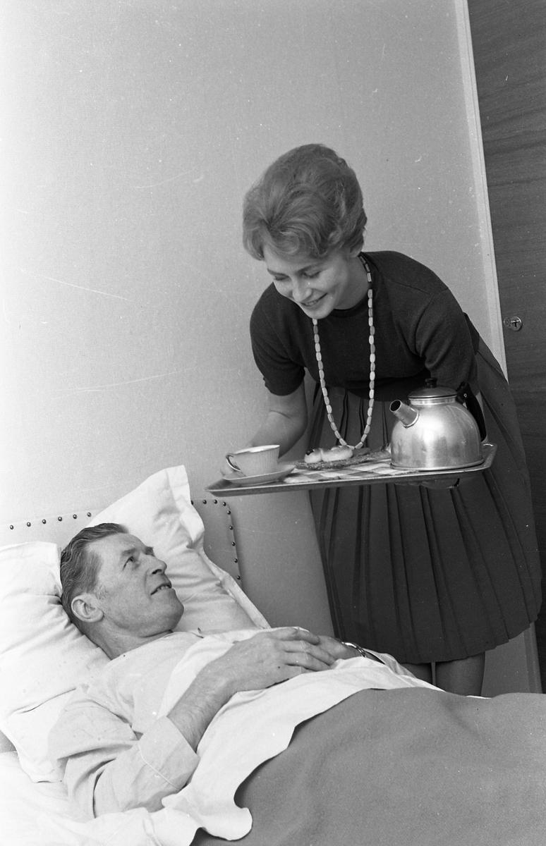 Kerstin Eklund, Arbogas Lucia, bjuder på kaffe på sängen. På Kerstins bricka finns en kaffepanna, en kaffekopp och en lussebulle, möjligen skymtar en pepparkaka. En man ligger i sängen. 1960-talet