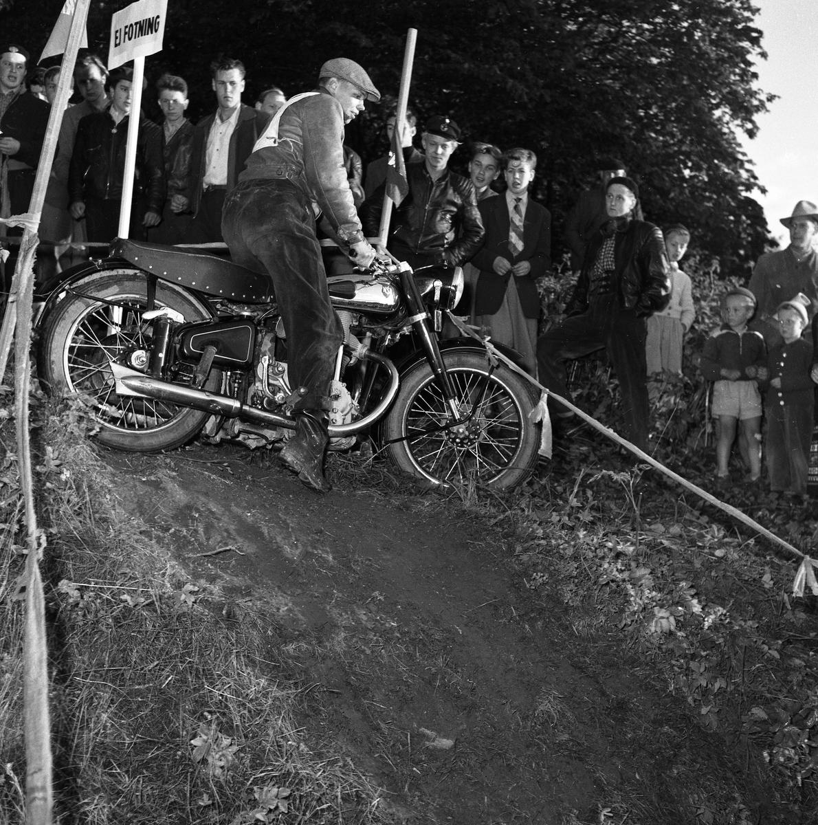 Arbogas Stjärnknutte Tävling i terrängkörning med motorcykel. Här står motorcykeln på tvären i nerförsbacken. Publiken tittar intresserat på.