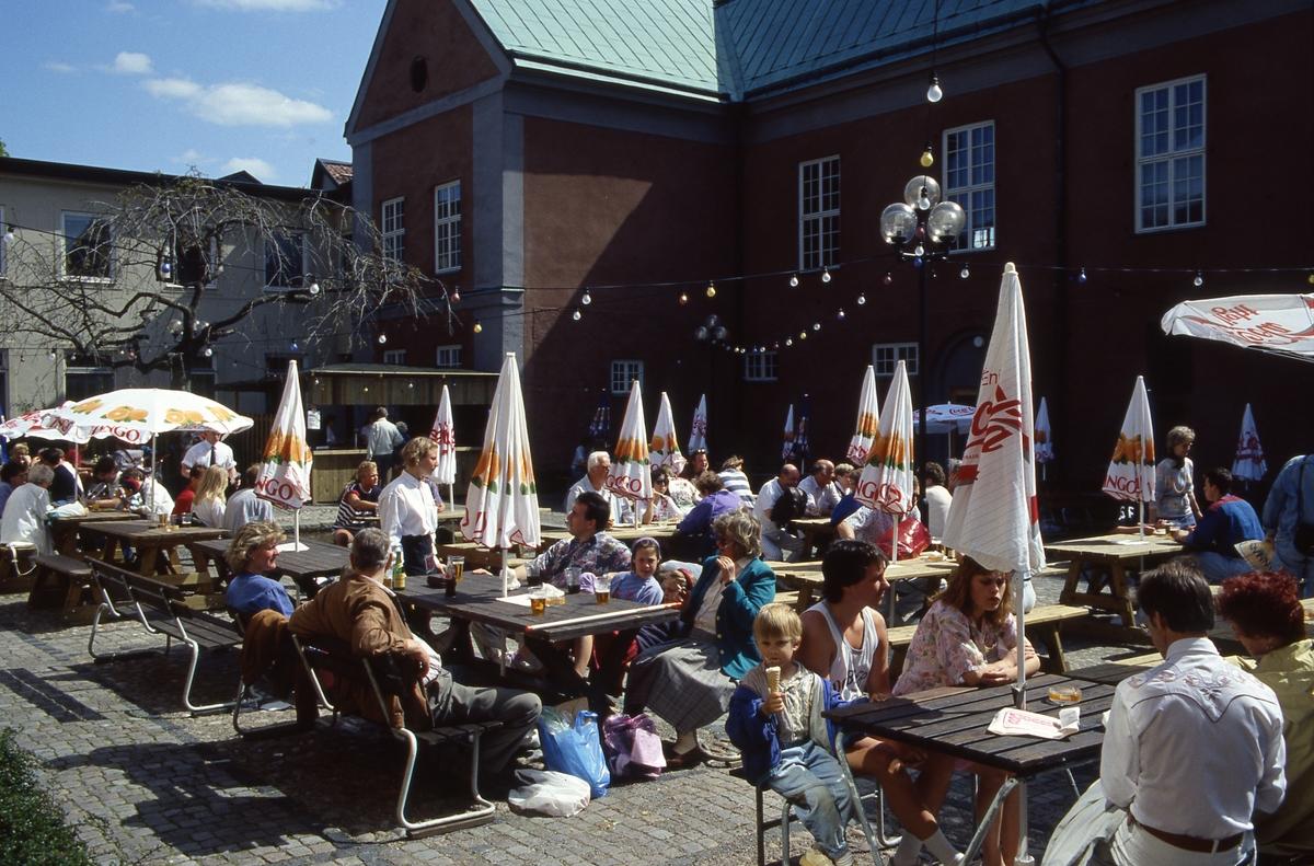 Arbogaträffen En tillfällig servering på Rådhusets innegård. Människor sitter på träbänkar och dricker öl och äter glass. Parasoll en är nedfällda.