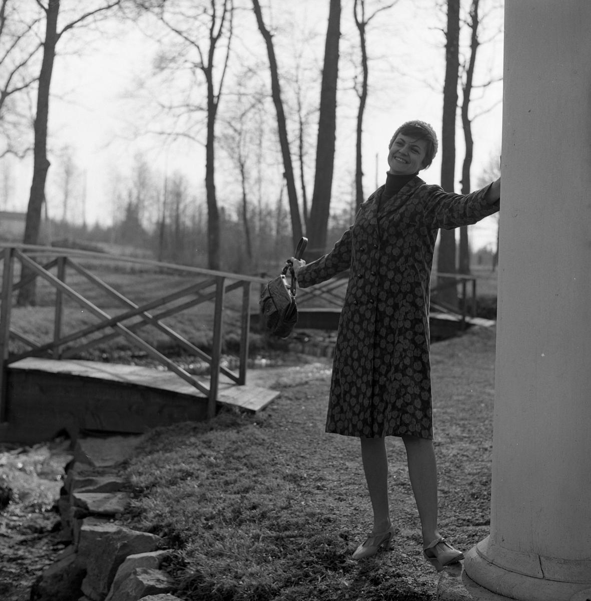 Ateljé Touche. Marianne Rosenqvist visar mode. Mönstrad kappa, mössa och handväska. I bakgrunden syns bäcken och ett par små broar.