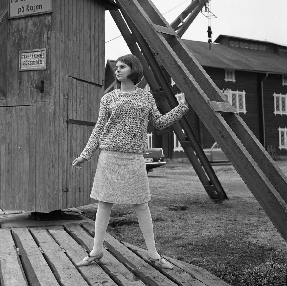 Ateljé Touche. En ung kvinna visar mode; jumper och kjol. Bilden är tagen i hamnen med hamnmagasin i bakgrunden.