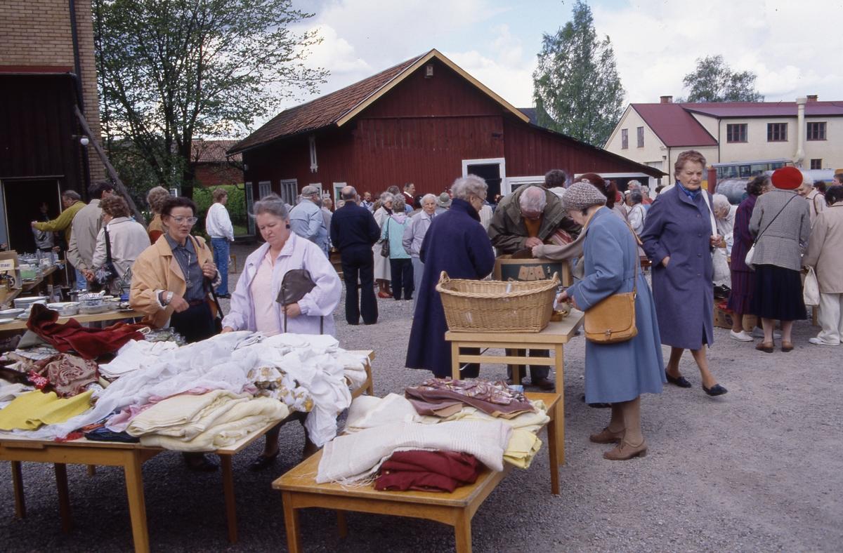 Auktion. Bord är uppställda på grusplanen. På borden ligger diverse textilier till beskådande. Många intresserade människor.