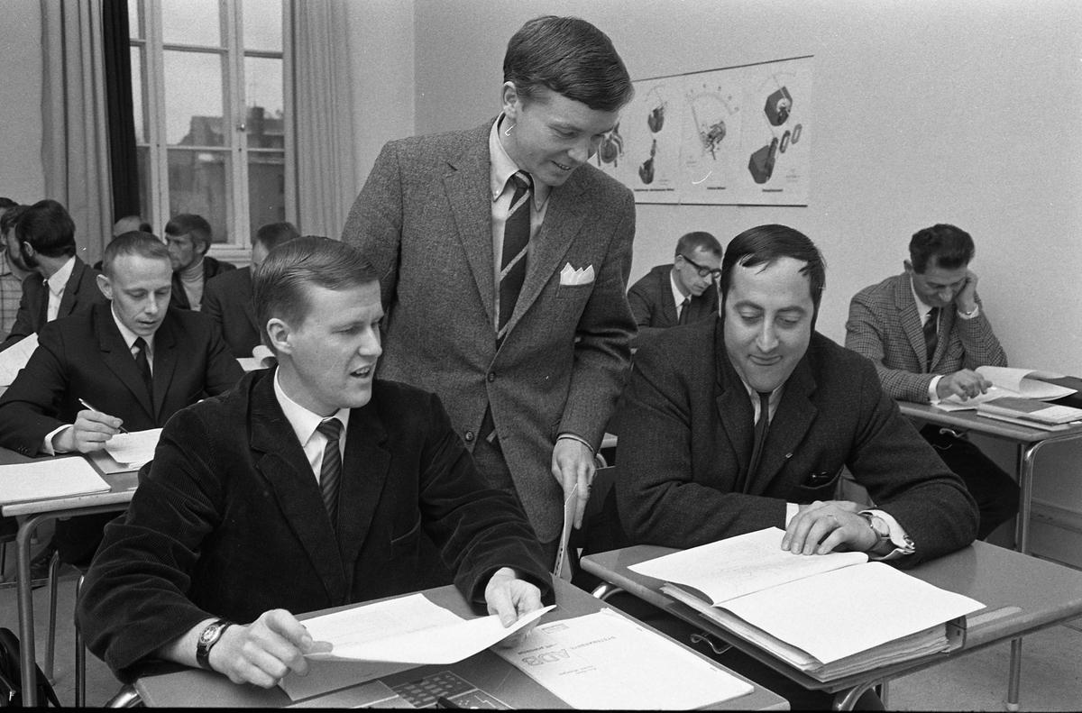 Avslutning på datakurs. Mannen som står upp heter Bertil Sund. Mannen längst till höger, i rutig kavaj, heter Walter. Kostymklädda män som sitter i skolbänkar. De har böcker och pärmar framför sig.