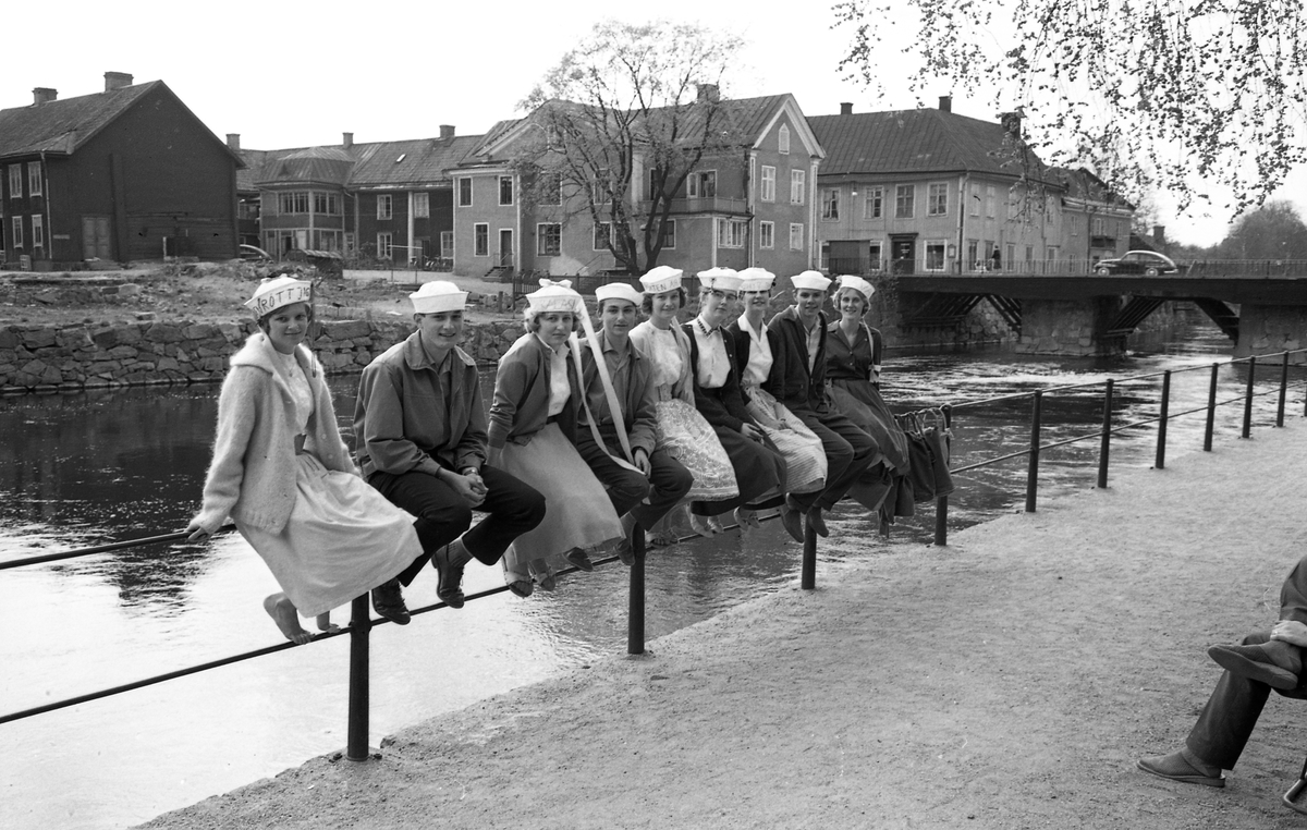 """Avgångselever från Arboga Samrealskola iklädda realmössor, våren 1960. Från vänster: Siv Österbacka, Gunnar Johansson, Gun Wadström, Åke Kjellmert, Ingela Mattsson, Lena Brorsson, Eva Pauly, Göran Bringby och Margareta Tegström. Sex unga kvinnor och tre unga män sitter på räcket mot Arbogaån. I bakgrunden syns kvarteret Garvaregården och Kapellbron. Den lilla """"kuren"""" vid södra brofästet är Simons korvkiosk. En PV kör över bron."""