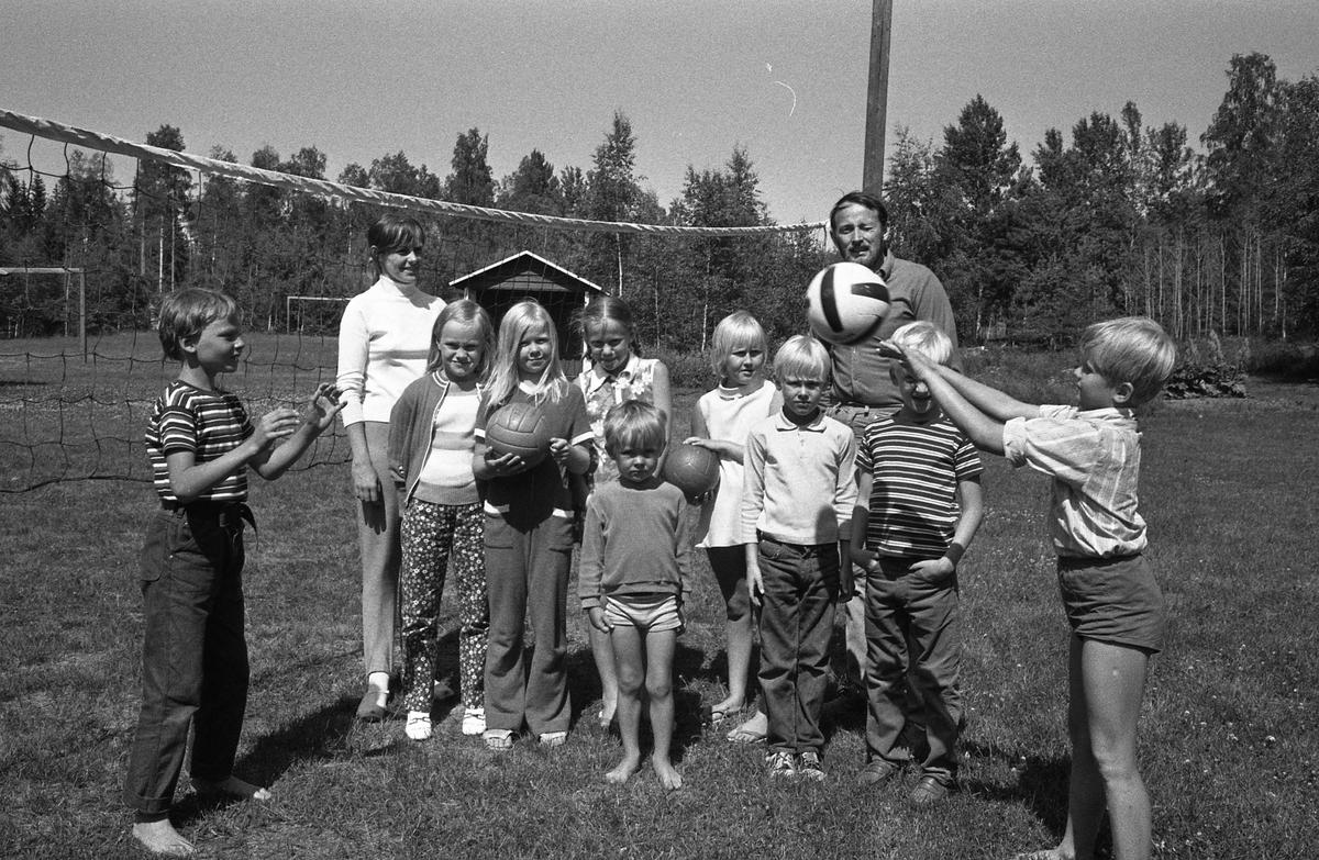 Barnens Dags koloni vid Högsjön, väster om Arboga. Flera barn och två ledare ska spela wolleyboll. Nätet är uppsatt. Flera bollar finns att tillgå. I bakgrunden skymtar en campingstuga.