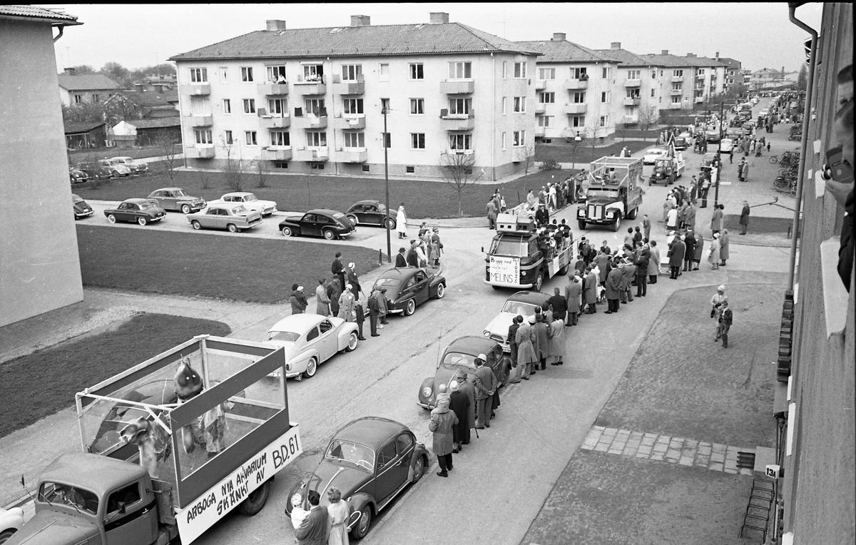 Barnens Dag firas med parad genom staden. Här ses kortegen av lastbilar, på Österled. På flaket finns utklädda människor som gör reklam för firmor i staden. Flerfamiljshusen ligger i kvarteret Långa Raden. Till höger, i förgrunden, ses en man med filmkamera.