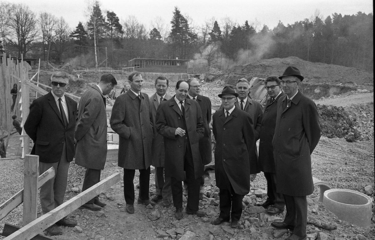 Herrar i vit skjorta och slips ser på byggplatsen för det nya badet i Ekbacken.  Utomhusbassängen håller på att grävas ur. Två av männen är identifierade: Den sjätte mannen från vänster är Hildning Lund och den åttonde är Nils Brodin. Till vänster i bild ses några ungdomar som sysslar med byggnationen.