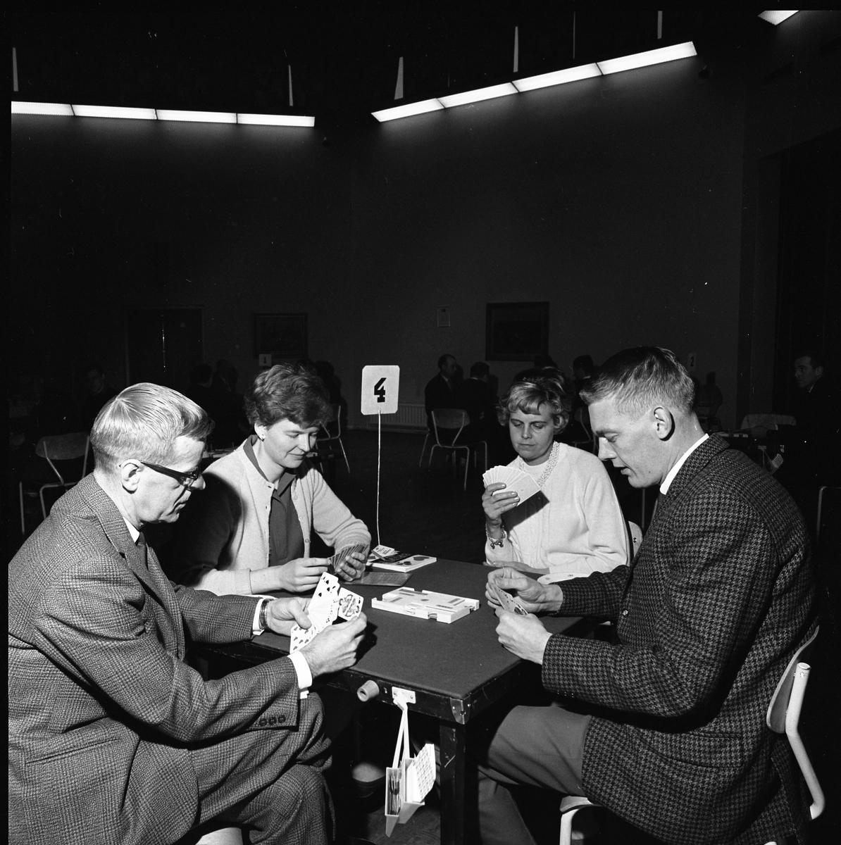 Bridgeklubben. Två kvinnor och två män vid tävlingsbord nummer fyra.