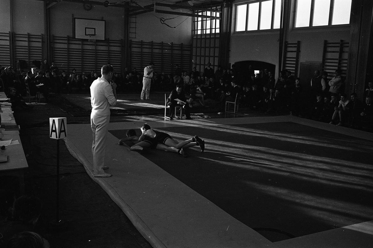 Brottning för ungdomar. Det pågår två tävlingar samtidigt. Platsen är en gymnastiksal. Publiken sitter längs väggarna.
