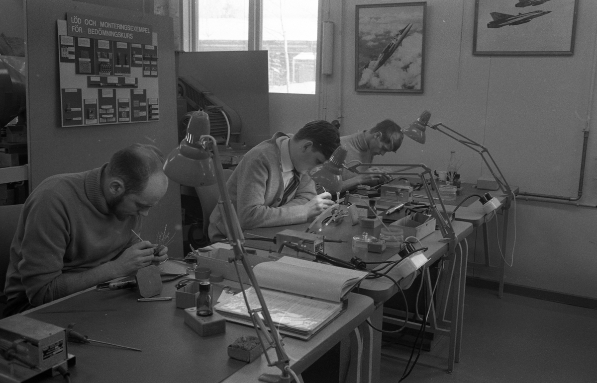 Tre män går på kurs i lödning på CVA. De har verktyg och skrivbordslampa på arbetsbordet. Centrala Verkstaden Arboga