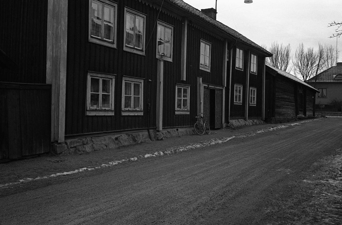 Tvåvånings bostadshus i trä. Adressen är Paradisgränd. Bortanför huset ligger ett uthus/förråd. Fotografens anteckning: Dokumentation av fastigheter i kvarteren söder och norr om ån. Bilder och beskrivning finns på Arboga Museum.