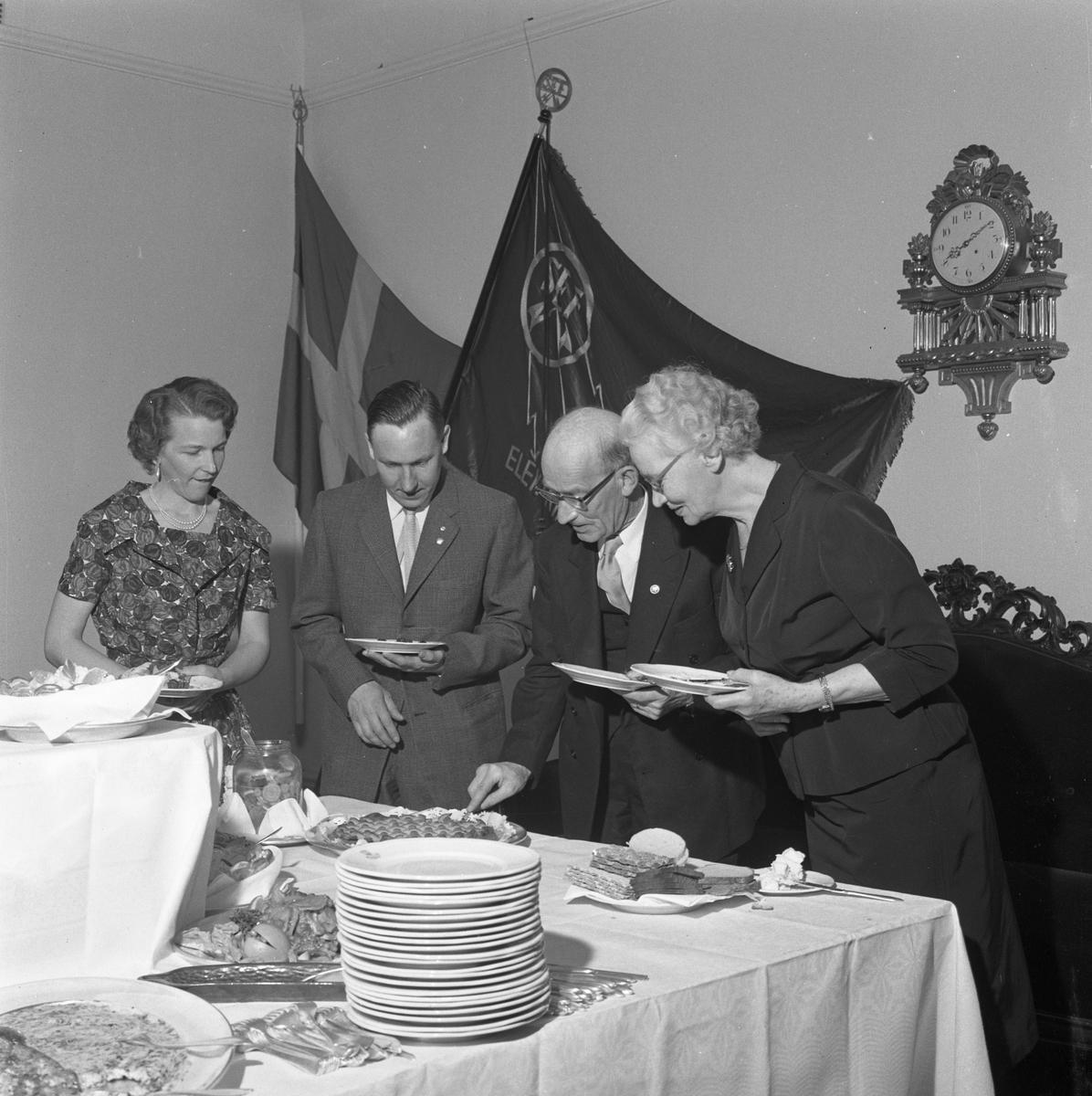 Elektrikerförbundets Arbogaavdelning har jubileumsfest. Gående bord. Två kvinnor och två män tar för sig av maten. På väggen hänger två fanor och en pendyl.