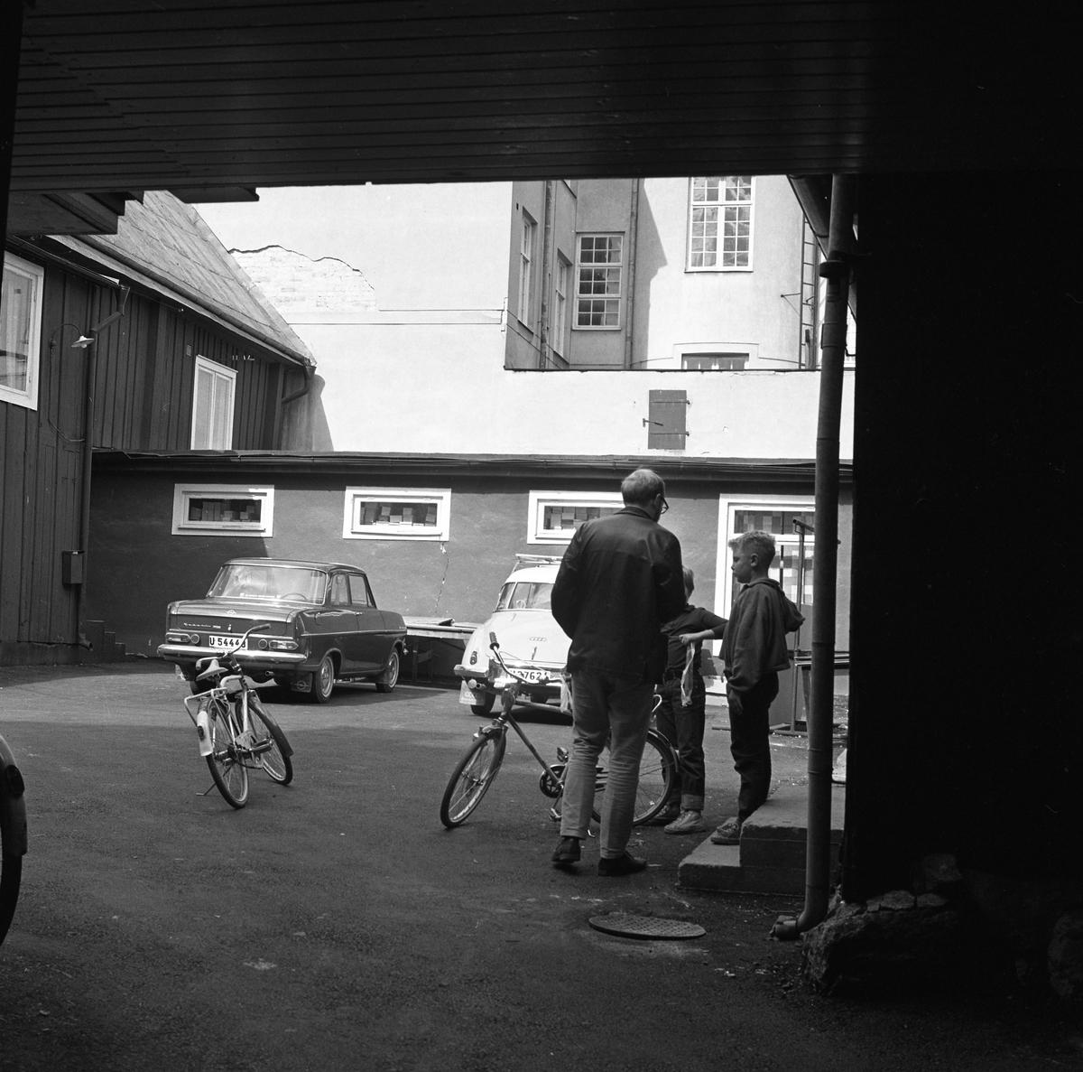 Arboga Tidning gör en enkät om skolan. En journalist intervjuar skolbarn. Platsen är en innegård med bilar och cyklar parkerade.