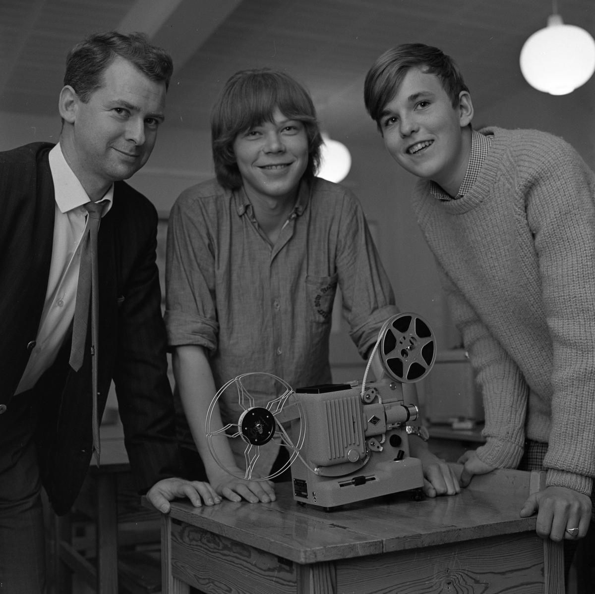 Filmgrupp på Stureskolan. Läraren heter Leif Ullström och eleverna är Kenneth Jansson och Claes Wadsten.  (Kenneth spelar i bandet Don Pedro). De står intill en filmprojektor som står på en skolbänk.