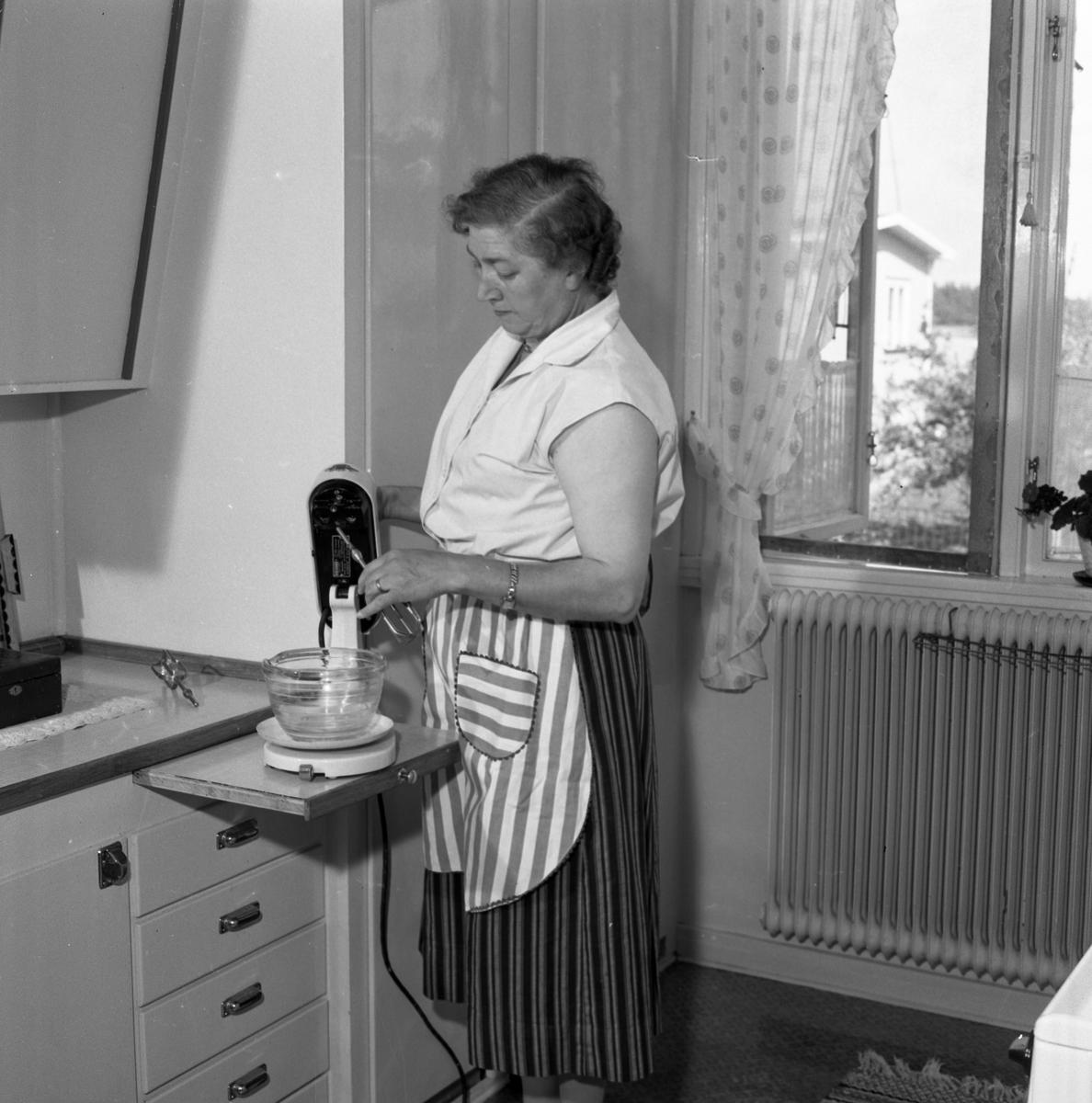 Fru Blomberg i köket. Hon är iklädd ett förkläde och har just tagit fram en skål och en el-visp. Fönstret är öppet och hon har myggnätet isatt. En krukväxt står på fönsterbrädan. Kvinnan är gift med Jakob Blomberg som arbetar på Arboga Mekaniska Verkstad. AMV