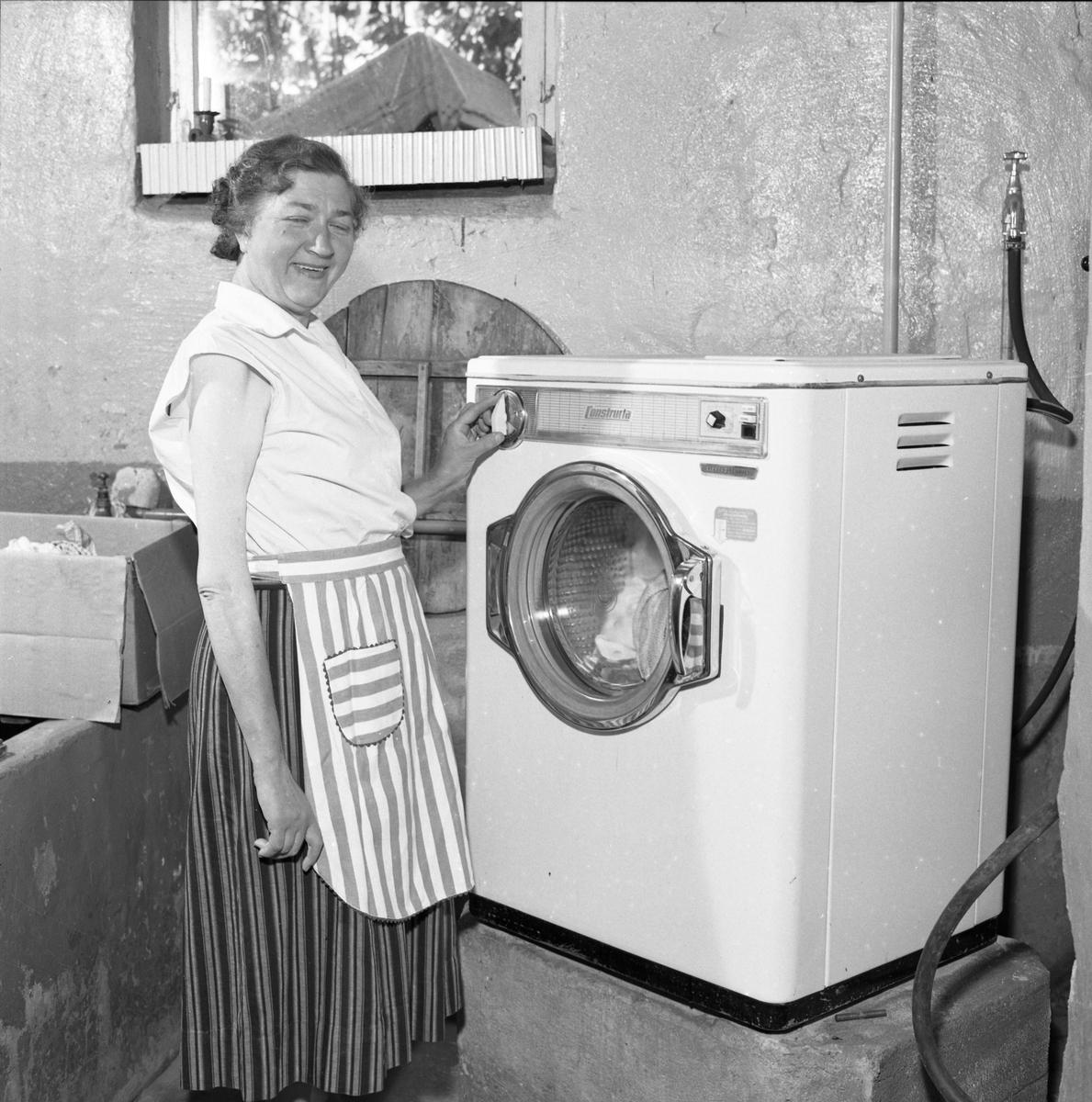 Fru Blomberg (hustru till Jakob Blomberg på Arboga Mekaniska Verkstad) visar en tvättmaskin. Kvinna, iklädd förkläde, står i källaren intill en ny tvättmaskin. AMV