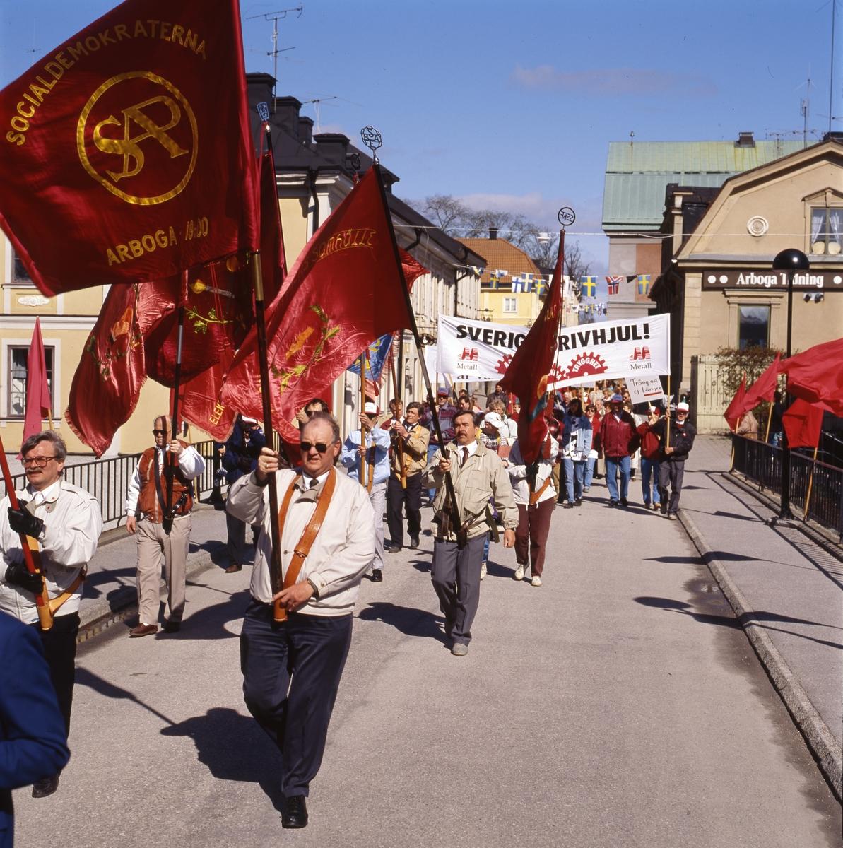 Första maj. Demonstrationståg på Kapellbron. Längst till vänster ses Börje Sturk. Människor marscherar med röda fanor och plakat. I bakgrunden ses kvarteret Stadsgården till vänster och Kungsgården till höger. socialdemokrater Socialdemokrater.