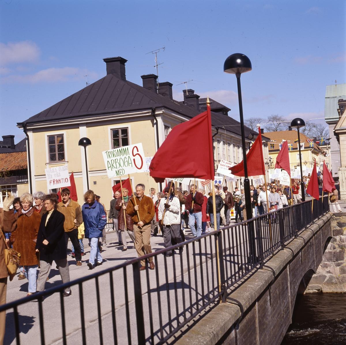 Första maj. Demonstrationståg på Kapellbron. Per-Olov Nilsson, i brun jacka, bär ett plakat. Kapellbron är dekorerad med röda fanor. Människor bär plakat. I bakgrunden ses kvarteret Stadsgården.