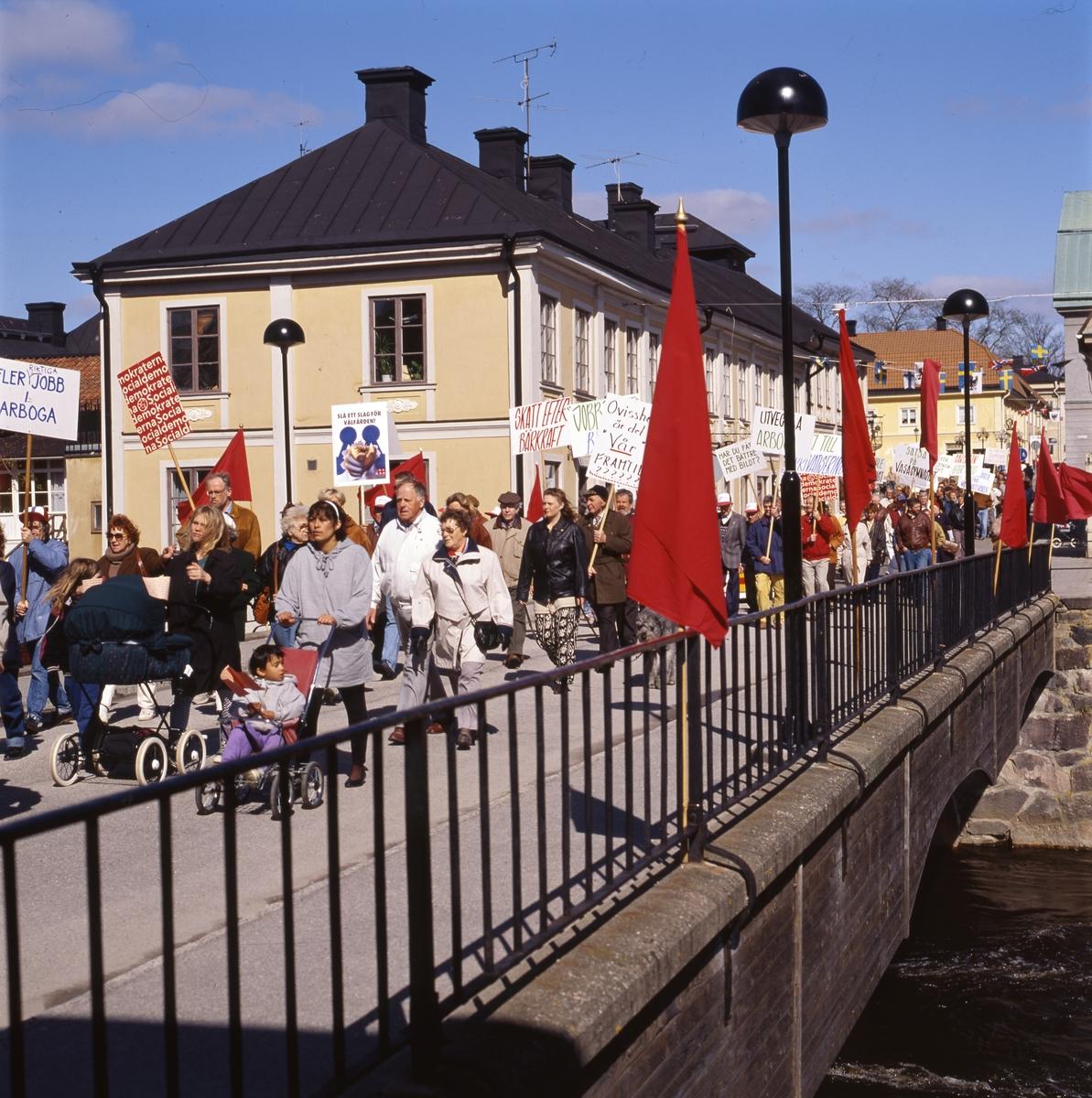 Första maj. Demonstrationståg på Kapellbron. Människor bär plakat. Bron är dekorerad med röda fanor. I bakgrunden ses kvarteret Stadsgården. Socialdemokrater.