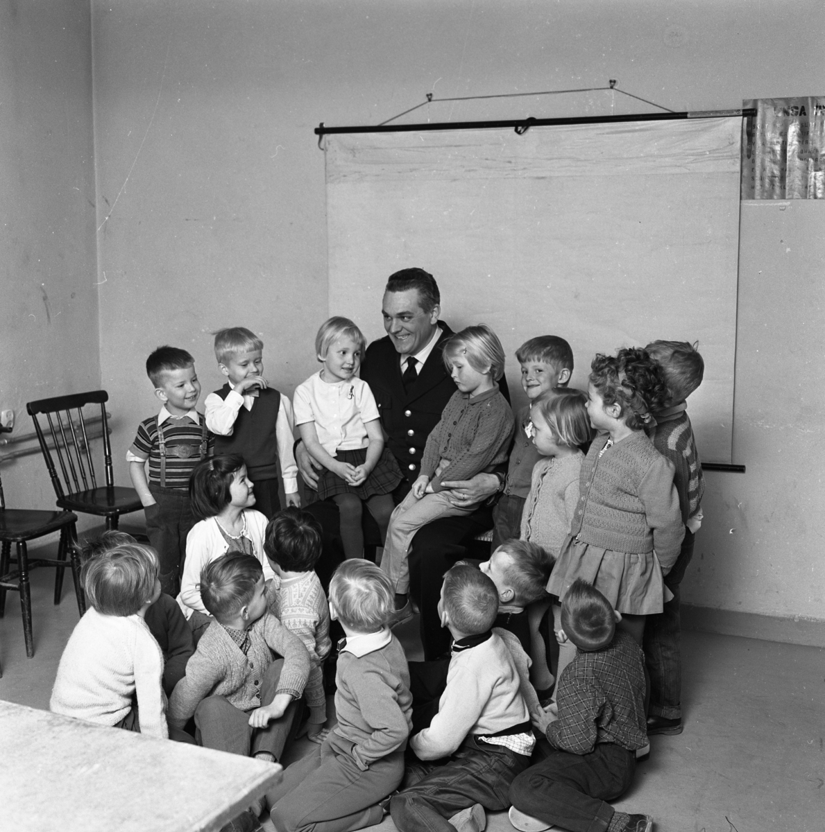 HSB´s lekskola har avslutning med besök av polis Ragnar Hedin. Barnen är samlade runt Ragnar som sitter med en flicka på varje knä. (HSB betyder Hyresgästernas sparkasse- och byggnadsförening)