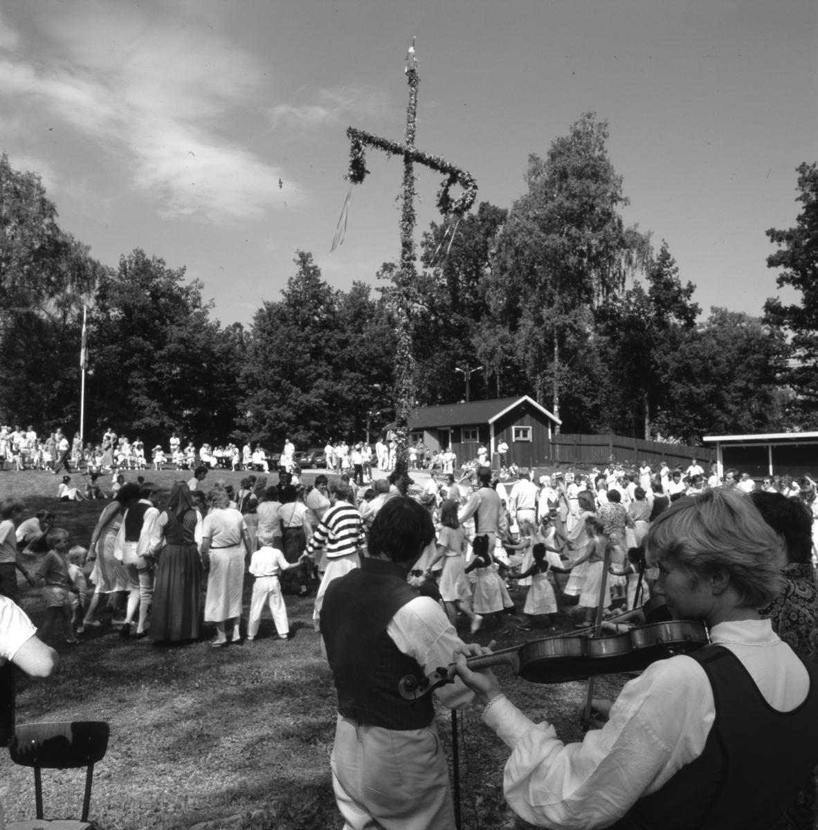 Midsommarfirande i Arboga Folkets park. Unga och gamla dansar kring midsommarstången. Spelmännen står närmast kameran. Längre bort finns kiosken där man kan köpa glass. Människor sitter i gräset eller i medhavda campingstolar. Flaggan är hissad och solen skiner.