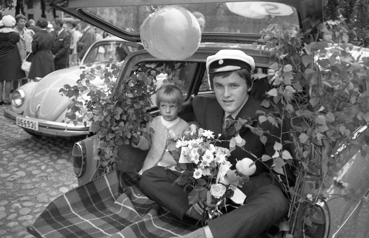 Studentdag! Bertil Pell körs runt i lövad och ballongförsedd baklucka. Som sällskap har han en liten flicka. Bertil har studentmössan på och famnen full av blommor. En folkvagn skymtar i bakgrunden.