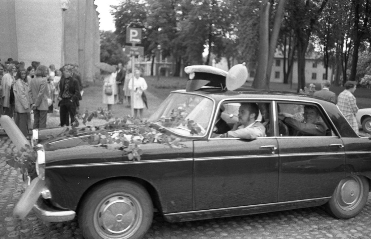 Studentdag! En bil är dekorerad med en stor studentmössa, björklöv och ballonger. I bakgrunden ses människor som samlats i Kyrkparken.