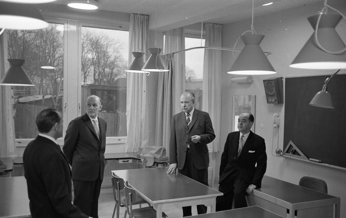 Invigning av Stureskolan. Fyra kostymklädda herrar bland skolbänkar och stolar i ett klassrum. Mannen med ryggen mot fotografen är troligen Tore W Ekman. Bredvid honom står rektor Bror Gustavsson. De andra två är okända.