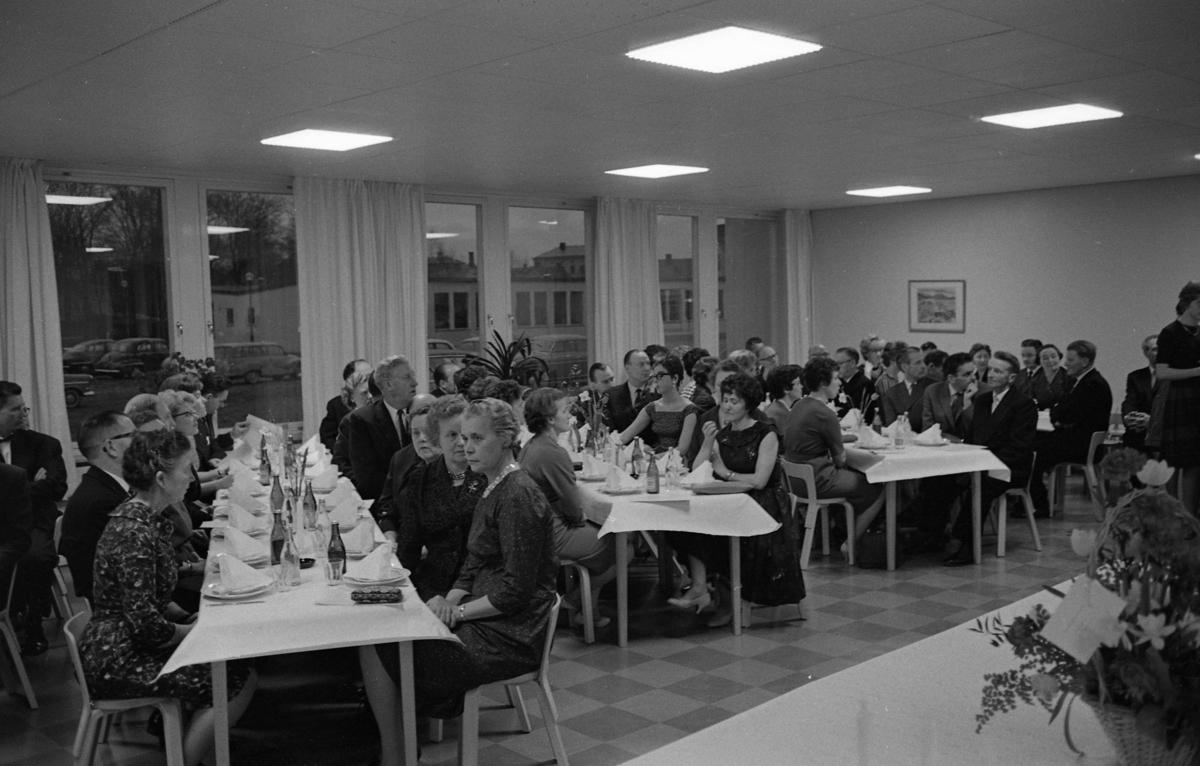 Invigningsfest på Stureskolan. Vid dukade bord sitter festklädda damer och kostymklädda herrar. Kvinnan i bildens nedre, vänstra hörn, kan vara Karin Gustafsson, rektor Bror Gustafssons hustru. Mannen på andra sidan hennes bord, är Folke Pettersson, lärare. Vid nästa bord, ses Bertil Karlsson närmast fönstret. Bredvid honom sitter Öhling. Mannen som ses i profil, i bildens övre högra hörn, är Torsten Karlsson, vaktmästare på Stueskolan.