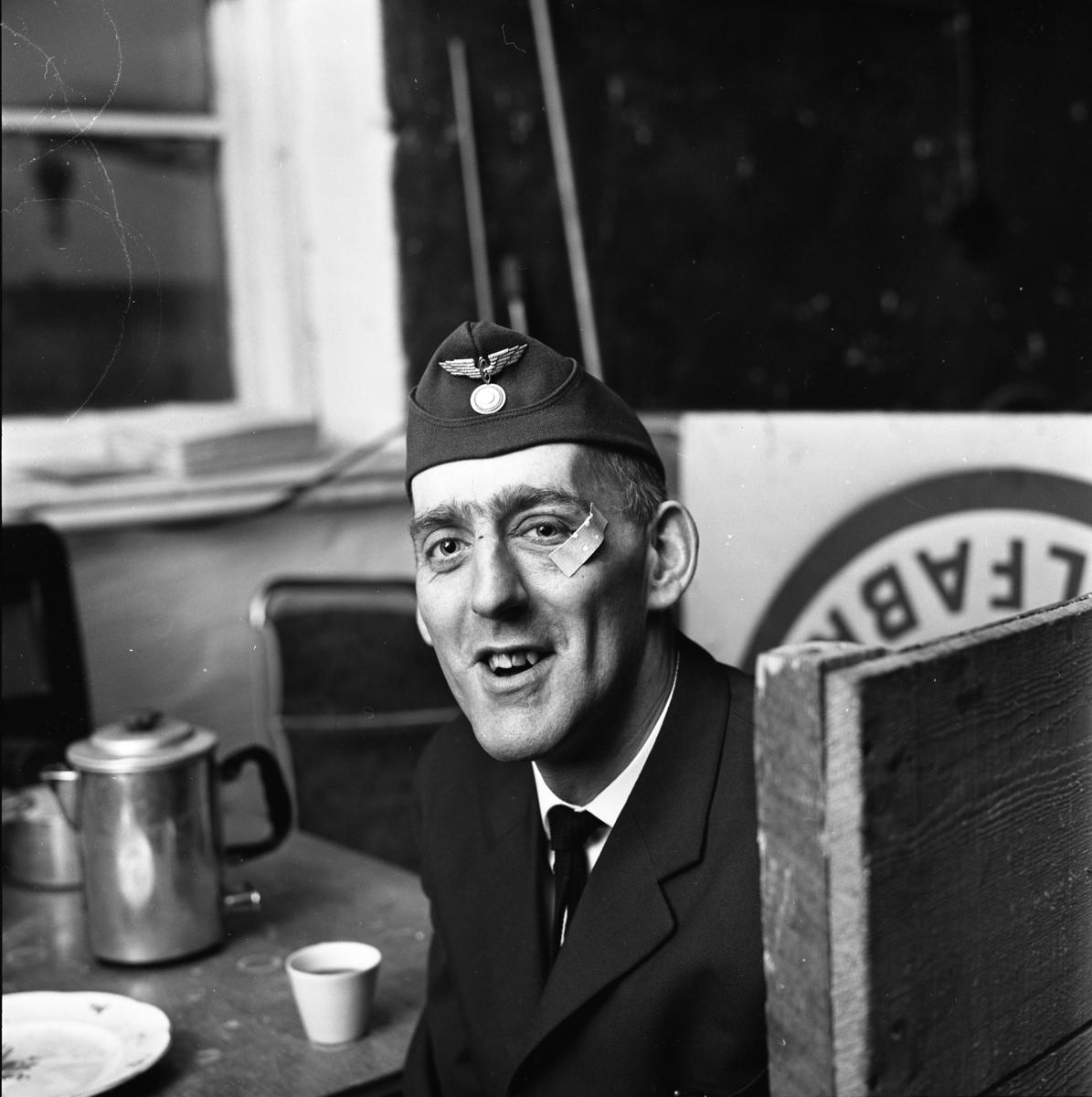 Arne Fallkvist/Arne Fallqvist har kafferast på taxistationen. En kaffepanna och en kopp står på bordet. Arne bär båtmössa. Han har ett plåster under ögat. Troligen skadade han sig under en ishockeymatch. Arne är en mycket duktig målgörare. Porträtt av man i arbetsuniform.