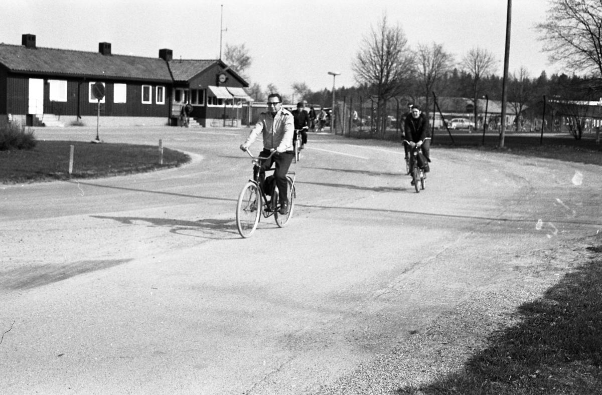 Männen cyklar hem från ännu en arbetsdag på CVA, Centrala Verkstaden Arboga. I bakgrunden ses byggnaden där vakten sitter och har kontroll på grinden som alla måste passera.