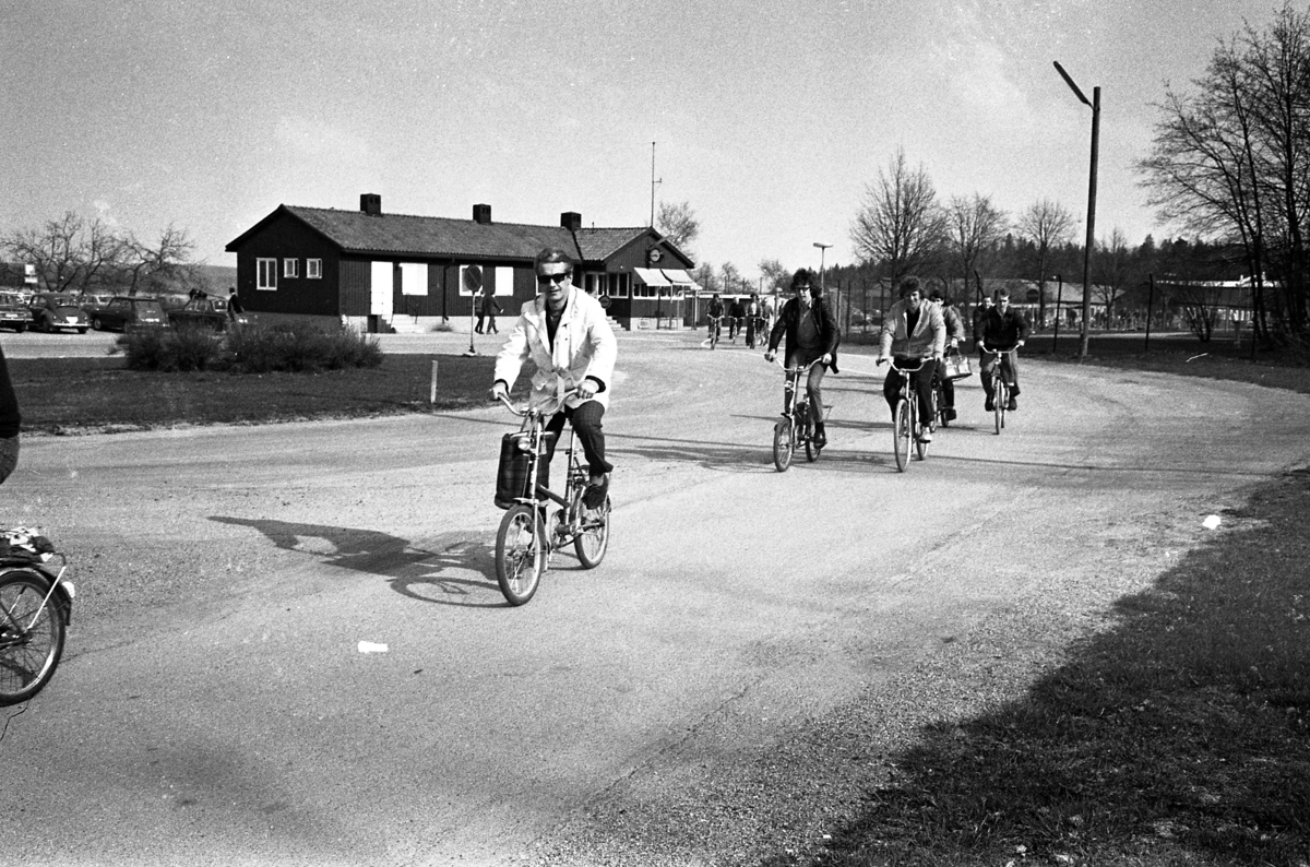 """Arbetsdagen är över på CVA, Centrala Verkstaden Arboga. Männen cyklar hem med sina matväskor på styret. Mannen längst till vänster är Ingvar Söderberg. Bakom honom kommer Hans-Erik Larsson (""""Vingis"""") och i bredd med honom cyklar Leif Andersson. Ingvar och Hans-Erik har minicyklar. I bakgrunden anas bilparkeringen. I byggnaden huserar vakten som kontrollerar grinden som alla måste passera."""