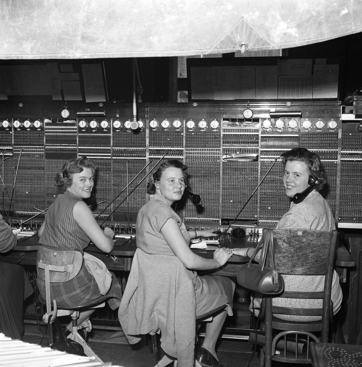 Televerket på Nygatan, efter branden. En presenning hänger i taket för att skydda växeln från det vatten som användes i släckningsarbetet. Växeltelefonisterna arbetar med en telefonlur hängande vid vänster öra. Klockorna, på rad, visar hur många perioder samtalen pågått. Från vänster: Britt Johansson, okänd och Mary Pettersson. Läs om Telefonen i Arboga och branden på Televerket 1956 i Arboga Minnes årsbok 1993.
