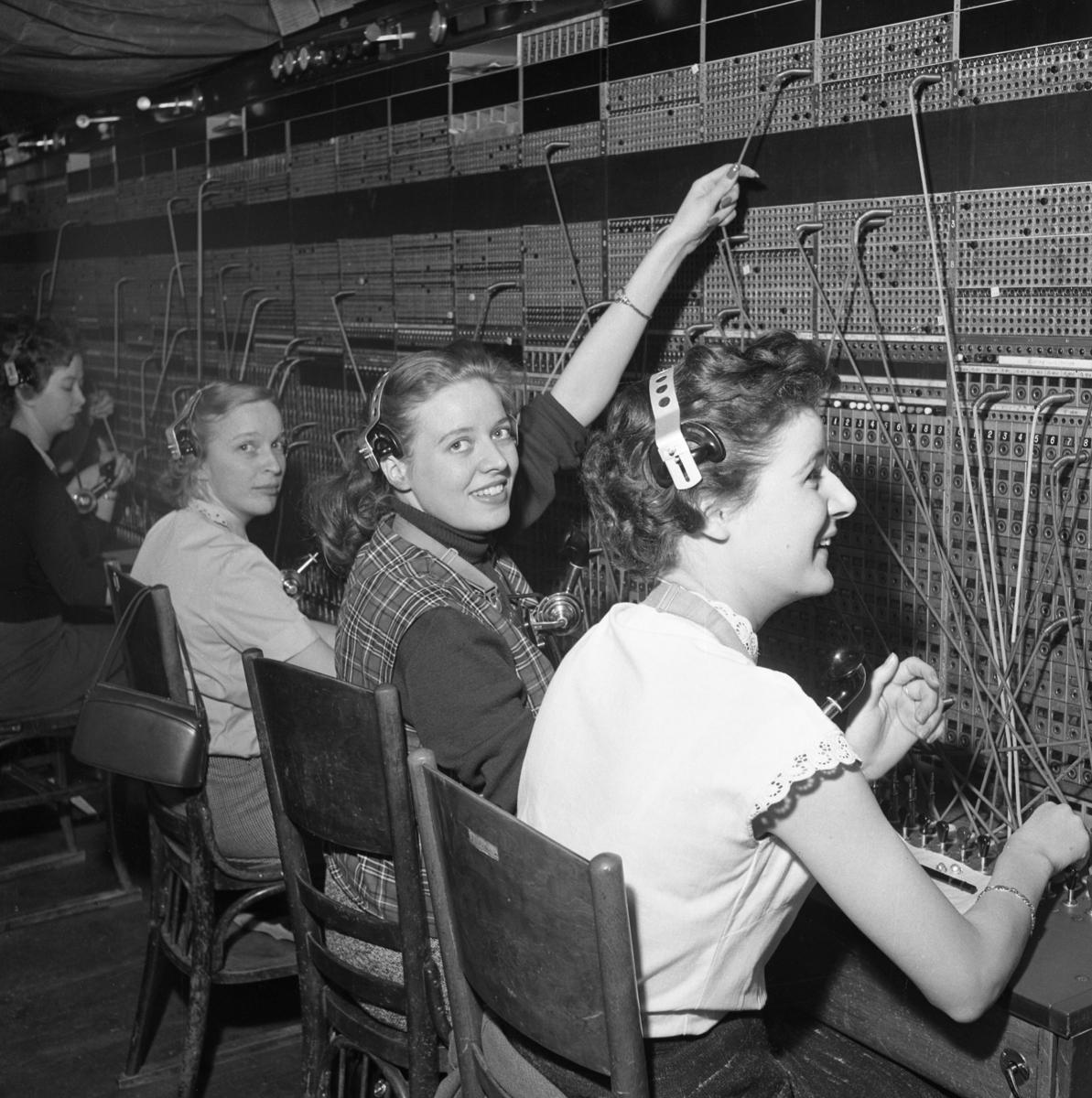 Trots brandskadorna i Televerket på Nygatan, fortsätter arbetet vid växelborden. Fyra växeltelefonister kopplar samtal.  Läs om Telefonen i Arboga och branden på Televerket 1956 i Arboga Minnes årsbok 1993.