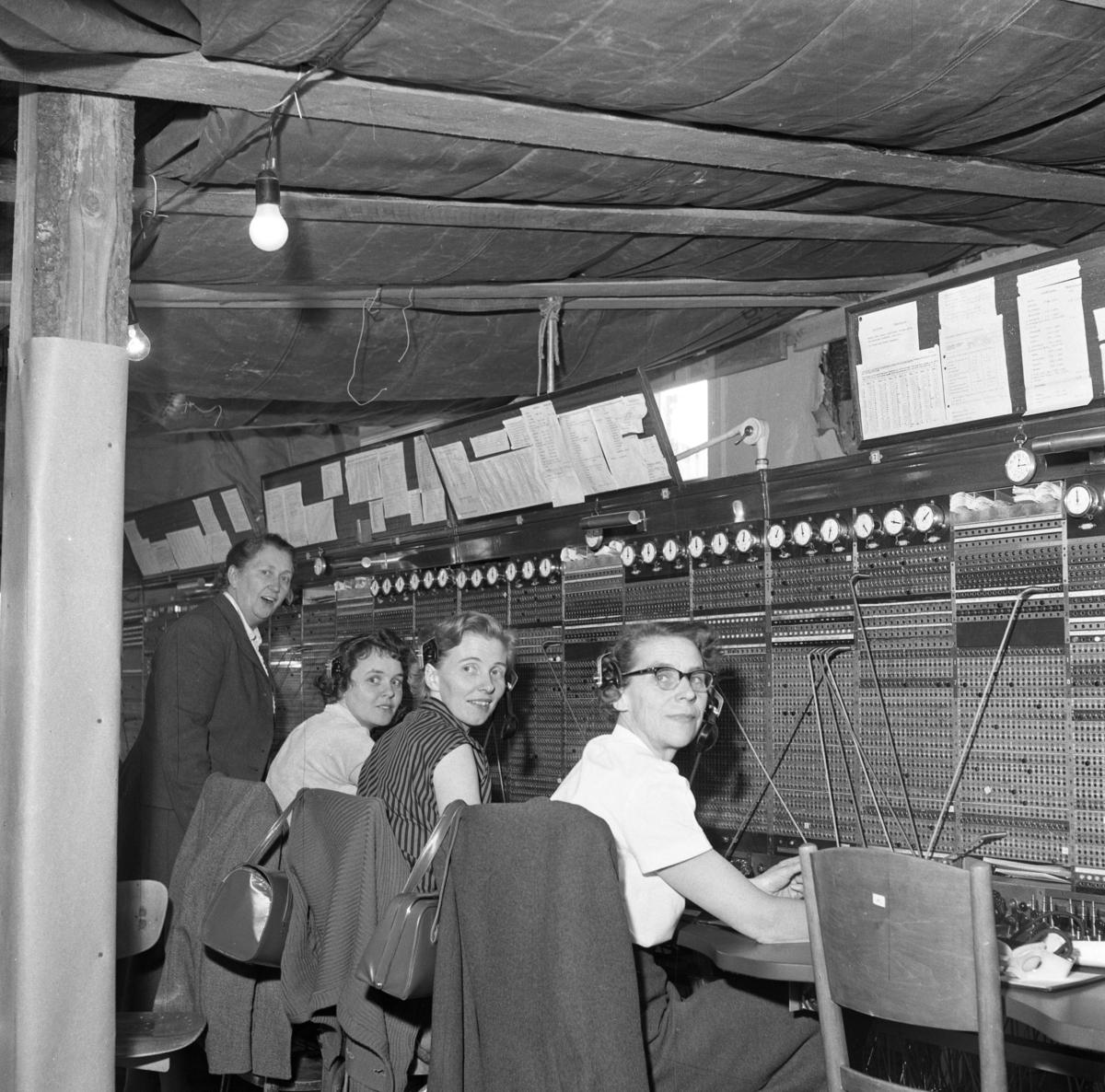 Det har brunnit i Televerkets lokal på Nygatan. Trots skadorna efter branden fortsätter telefonisterna sitt arbete vid växelborden. I taken hänger presenningar för att skydda växeln mot det vatten som användes i släckningsarbetet. I taket hänger nakna glödlampor. Läs om Telefonen i Arboga och branden på Televerket 1956 i Arboga Minnes årsbok 1993.