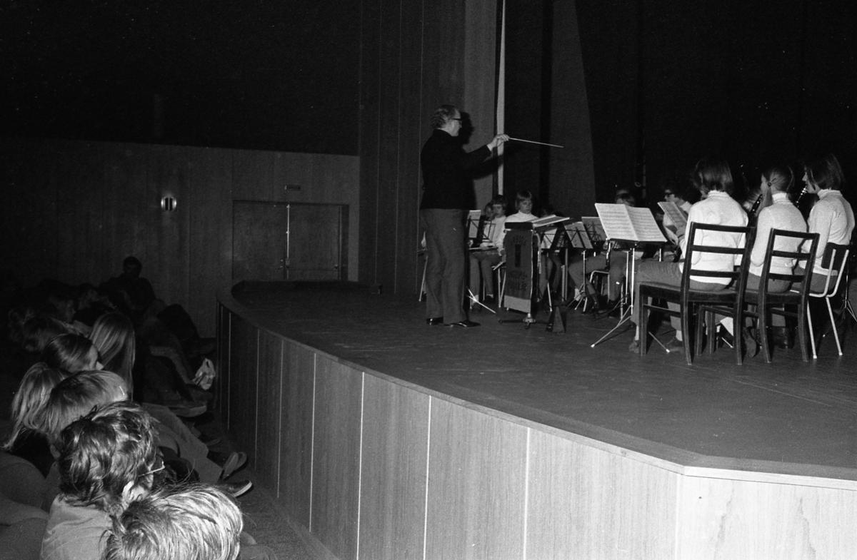 Ungdomsmusikkåren har konsert för andra ungdomar. Orkestern sitter på scenen på Medborgarhuset. Dirigent är Karl-Axel Göransson.