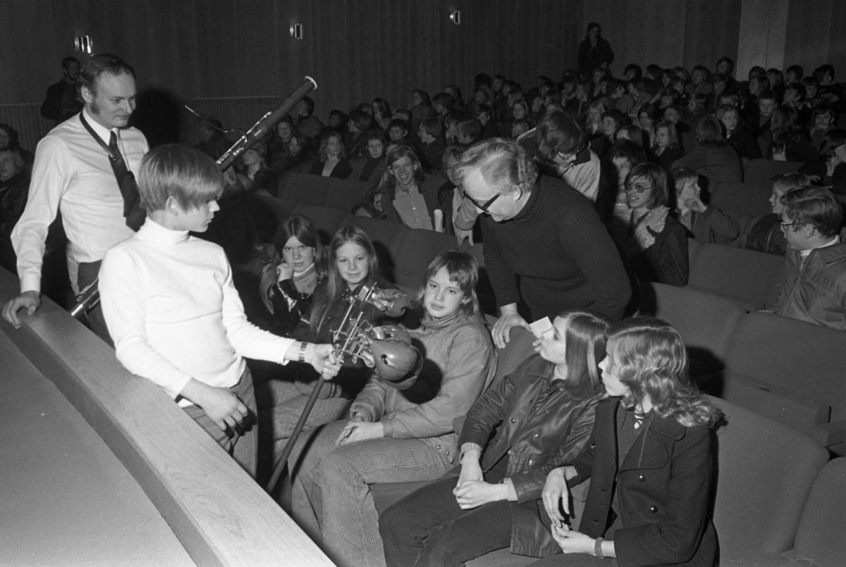 Ungdomsmusikkåren uppträder och visar sina instrument för andra ungdomar. Killen med fagotten heter Perry Göransson. Mannen med glasögon, är dirigenten Karl-Axel Göransson. Platsen är Medborgarhuset.