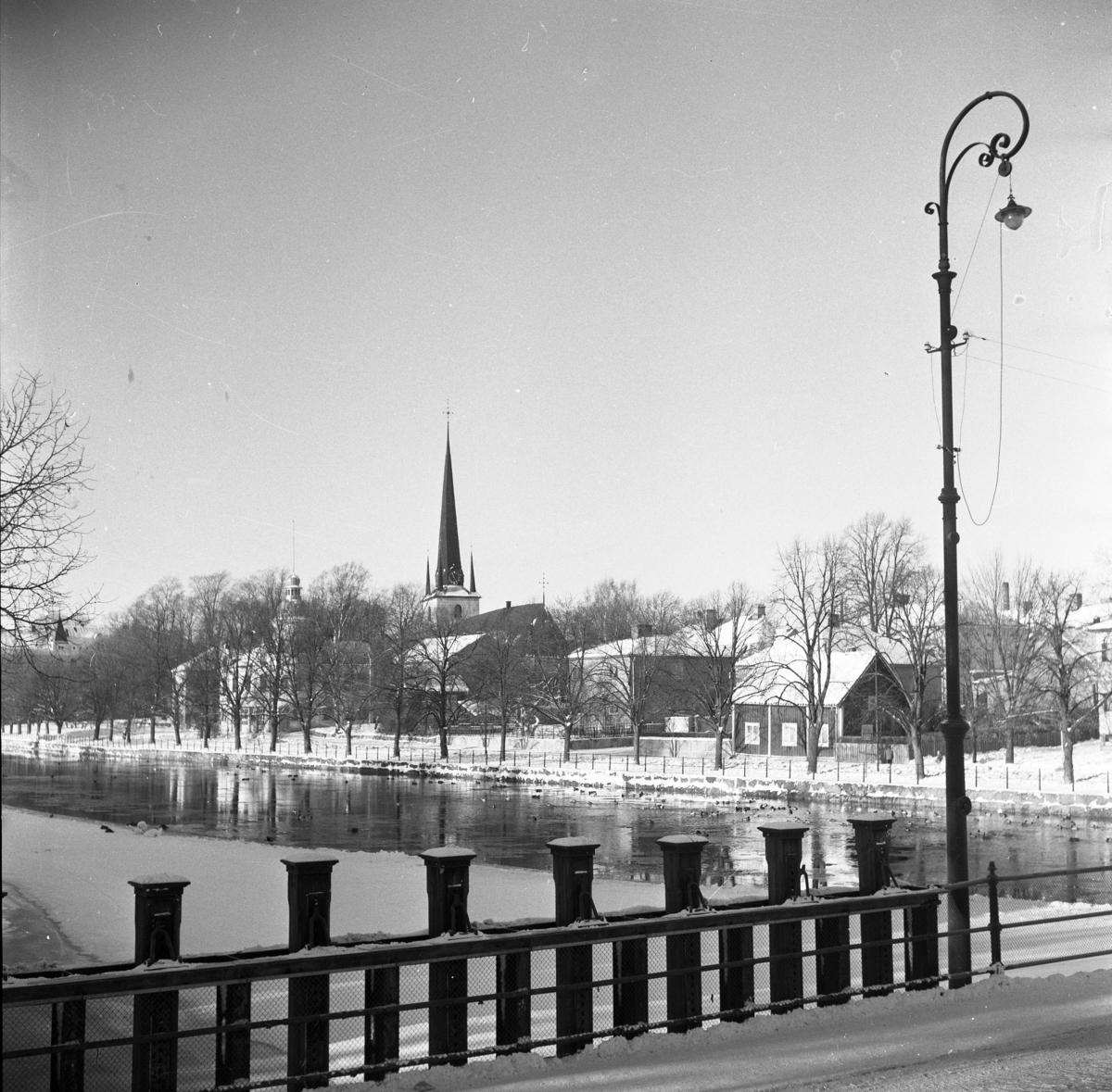 Vintermotiv från Herrgårdsbron. Utsikt över fastigheter på Strandvägen. Mitt i bild ses Heliga Trefaldighetskyrkan. Till vänster om den ligger Brandstationen. Det är vinter och snö. Broräcke och lyktstolpe.