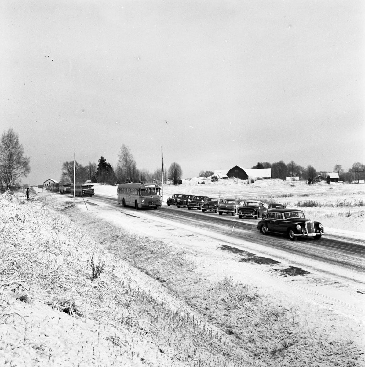 Örebrovägen öppnas efter ombyggnad En personbil och fyra bussar kör på vägen. Flera tomma bilar står parkerade vid sidan av. Det är vinter och snö.