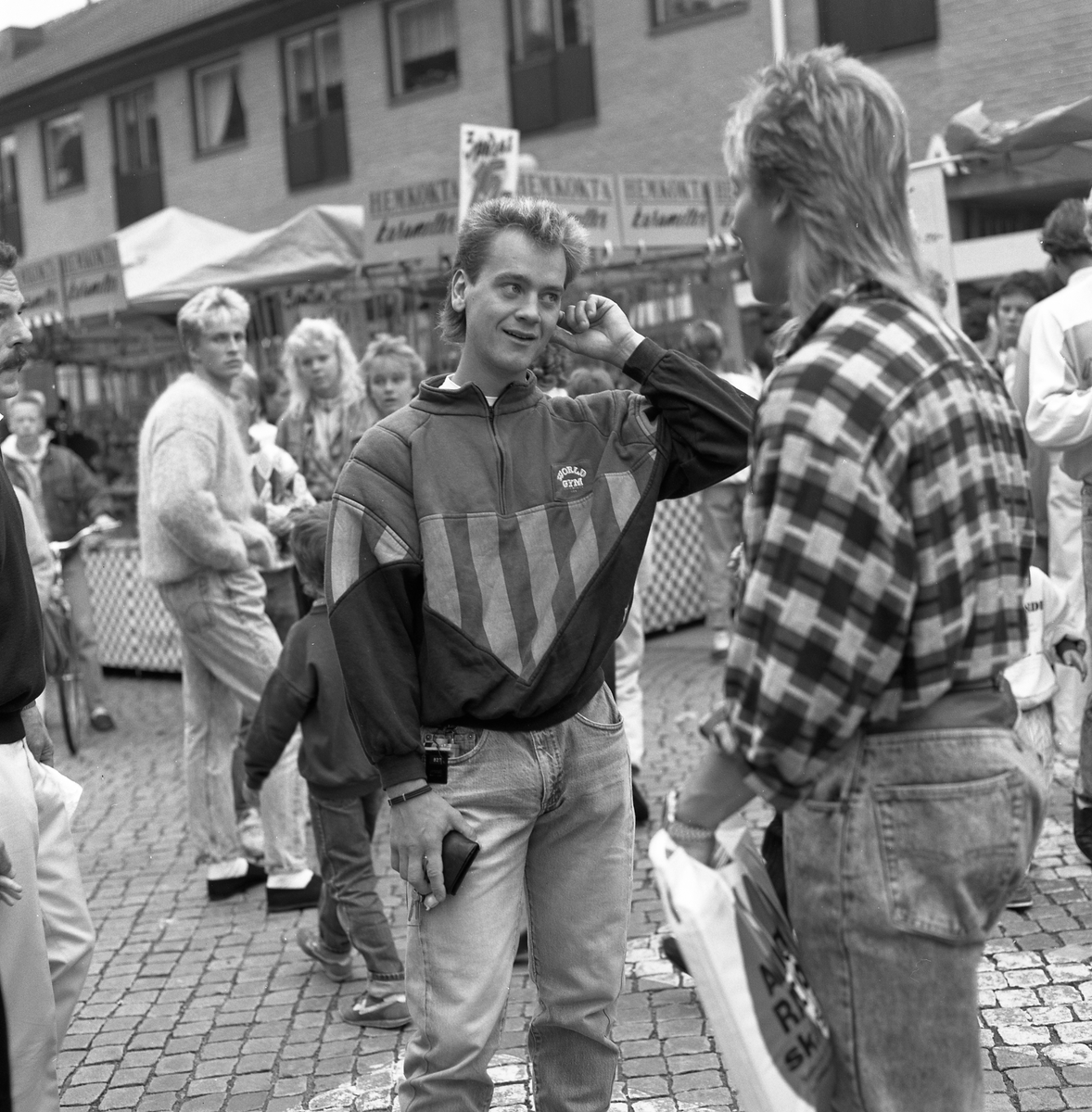 Höstmarknad på Järntorget. Två unga män samtalar. Den vänstra är Robert Andersson. Fler ungdomar i bakgrunden, längst till vänster står Peter Berg. Ett marknadsstånd med hemkokta karameller.
