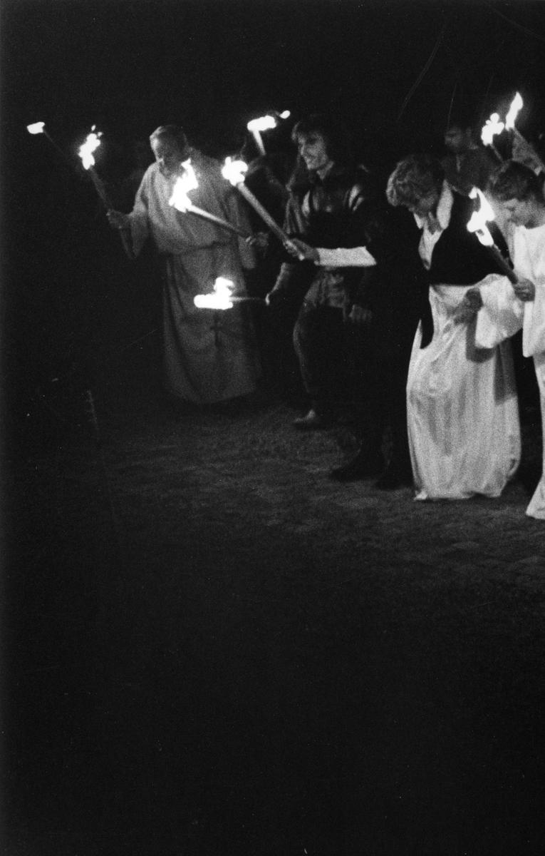 """Bygdespelets Vänner har just framfört skådespelet """"Giv oss fred"""" och tackar publiken för applåderna. I mitten ses rollfiguren Lasse Sommar. Platsen är museets innegård. """"Giv oss fred"""", även kallat """"Arbogaspelet"""", är ett teaterstycke skrivet av Rune Lindström 1961. Handlingen, som är inspirerad av Arbogas klosterhistoria, är förlagt till början av 1500-talet. Uruppförandet skedde den 11 augusti 1962 och Rune Lindström spelade Engelbrekt Gertsson. Lions Club i Arboga stod för arrangemanget. Föreställningarna regnade bort och det blev ett stort ekonomiskt bakslag för föreningen. Spelet har framförts igen; 1987, 1988, 2012 och 2015 av medlemmar i """"Bygdespelets Vänner""""."""