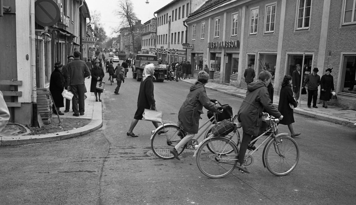 Folkliv på Nygatan. Cyklister, lastbilar och bilar. Människor som går på trottoarer och över gatan. På vänster sida ses skylten till Marks varuhus och Bröd-skylten. På höger sida ligger en bar, EPA, en tobaksaffär och Nils Adamssons.