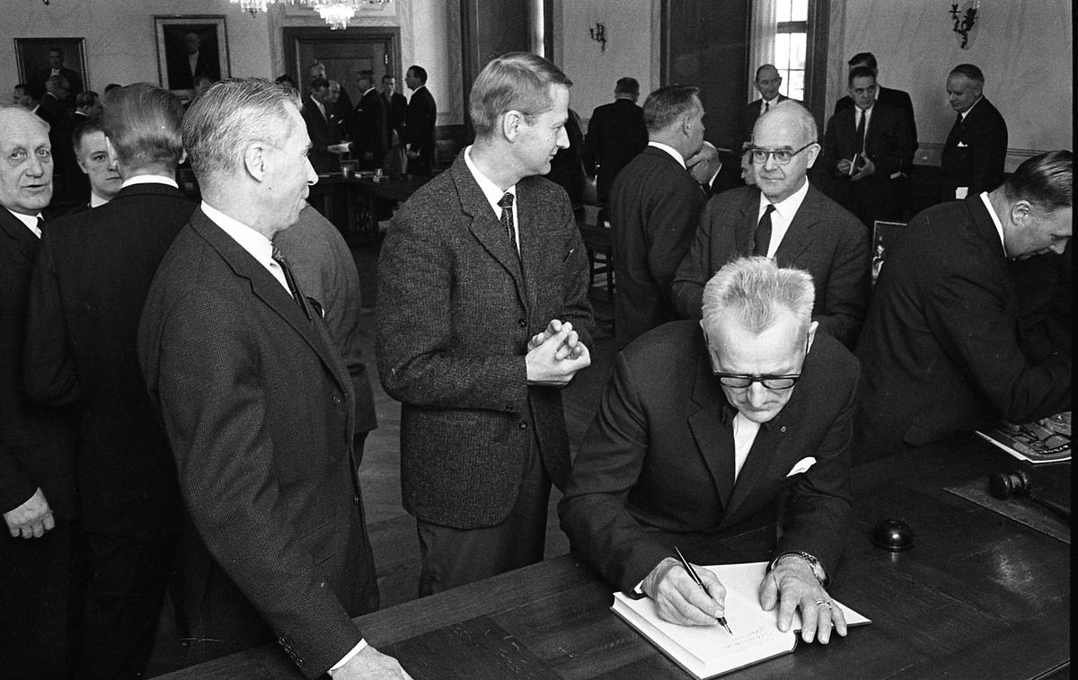 Statsutskottet besöker Arboga. Politikerna har möte i fullmäktigesalen på Rådhuset. Till vänster ses Harald Larsson (kallad Hajan). Utskottets ordförande, Gösta Bohman, har handen på bordet. Stadsfullmäktiges ordförande, Jonas Carlsson skriver i boken.