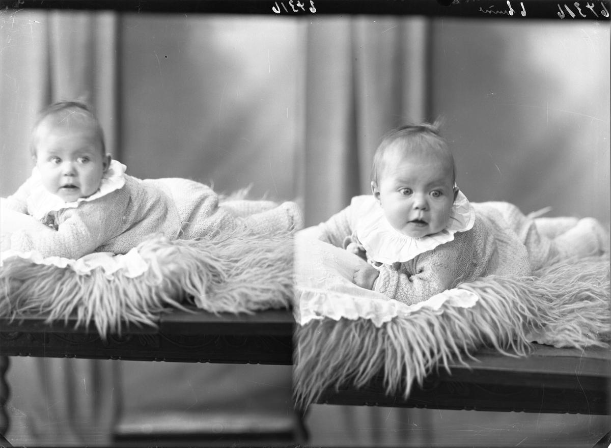 Portrett. Lite barn i lys strikket tøy med stor hvit krage liggende på en lys pels. Bestillt av Fru Pastor Haugland.